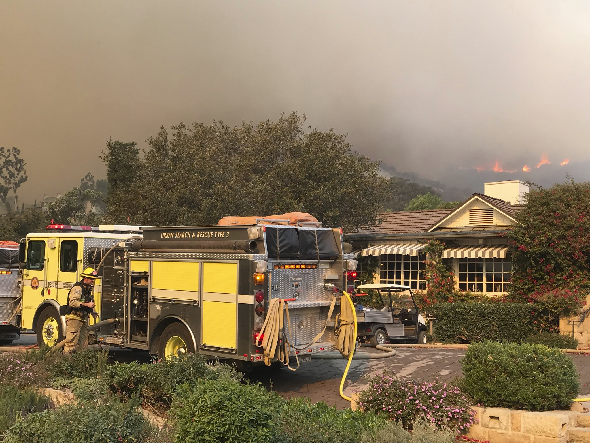 In this photo provided by the Santa Barbara County Fire Department, fire engines provide structure protection at the historic San Ysidro Ranch in Montecito, Calif., Saturday, Dec. 16, 2017. Santa Barbara County has issued new evacuation orders as a huge wildfire bears down on Montecito and other communities. The Office of Emergency Services announced the orders Saturday as Santa Ana winds pushed the fire close to the community.   (Mike Eliason/Santa Barbara County Fire Department via AP)