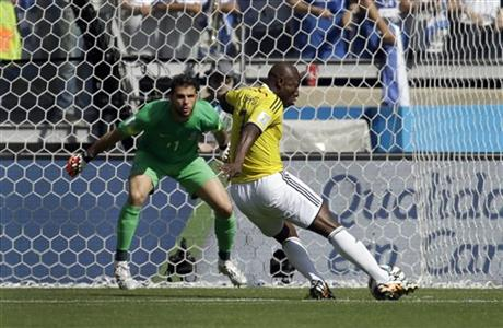 Colombia's Pablo Armero, right, kicks the ball at Greece's goalkeeper Orestis Karnezis to score his side's first goal during the group C World Cup soccer match between Colombia and Greece at the Mineirao Stadium in Belo Horizonte, Brazil Saturday.