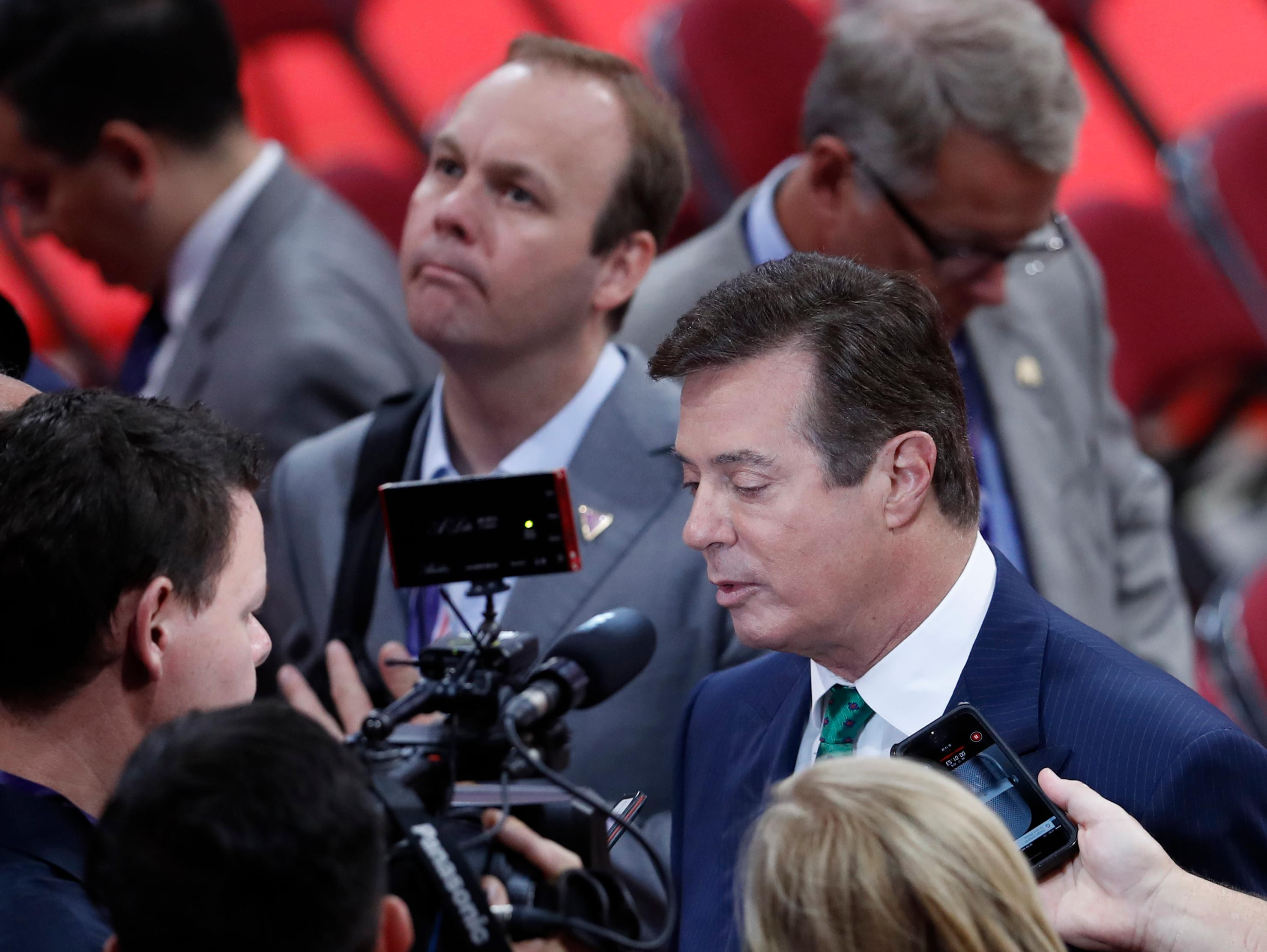 FILE - In this July 17, 2016 file photo, President Donald Trump's Campaign Chairman Paul Manafort is surrounded by reporters on the floor of the Republican National Convention in Cleveland. Rick Gates, a former business associate to Manafort and former campaign aide to Republican presidential candidate Donald Trump, is center rear.   (AP Photo/J. Scott Applewhite)