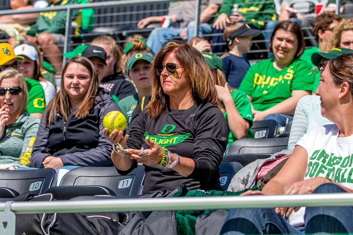 A fan in the crowd holds up a foul ball not knowing what to do with it. The fan would be able to turn it into the information desk after the game for a free mini-softball. The Oregon Ducks Softball team took their third win over the Arizona Sun Devils, 1-0, in the final game of the weekends series that saw the game go into an eighth inning before the Duck?s Mia Camuso (#7) scored a hit allowing teammate Haley Cruse (#26) to run into home plate for a point. The Ducks are now 33-0 this season and will next play a double header against Portland State on Tuesday, April 4 at Jane Sanders Stadium. Photo by August Frank, Oregon News Lab