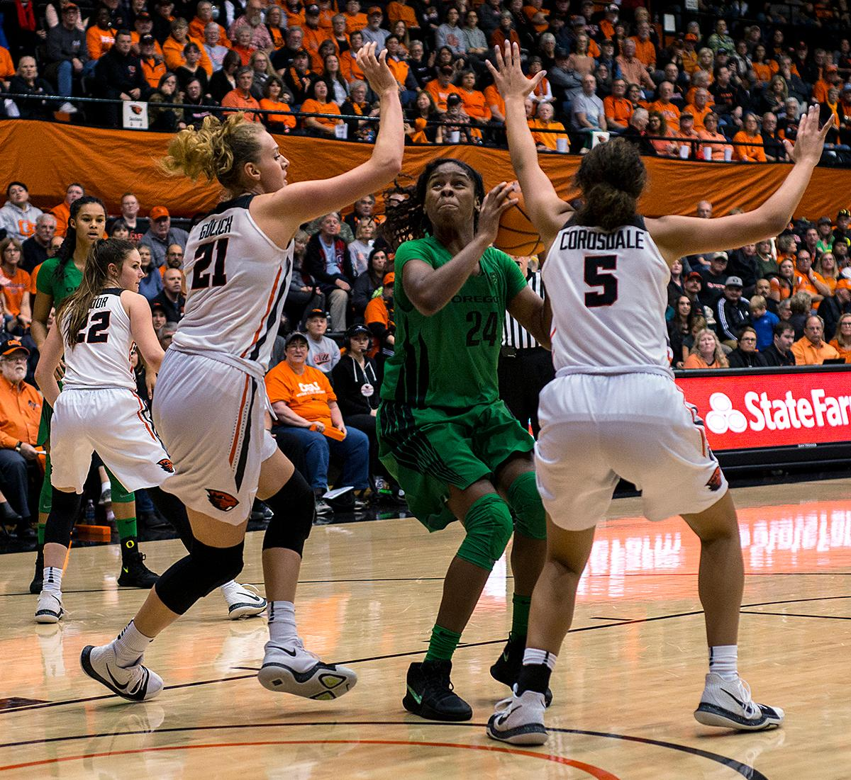 Oregon Ducks guard Ruthy Hebard (#24) tries to weave through Oregon State Beavers forwards Taya Corosdale (#5) and Marie Gülich (#21) as they defend their basket.The Oregon Ducks were defeated by the Oregon State Beavers 85-79 on Friday night in Corvallis. Sabrina Ionescu scored 35 points and Ruthy Hebard added 24. The Ducks will face the Beavers this Sunday at 5 p.m. at Matthew Knight Arena. Photo by Abigail Winn, Oregon News Lab