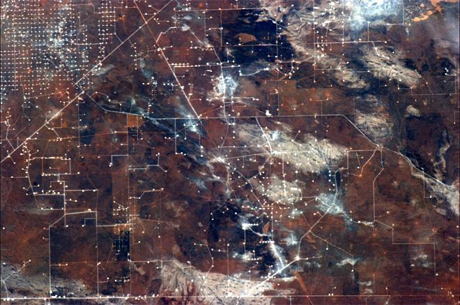Oil drilling draws a circuit board on the ochre landscape. (Photo & Caption: Chris Hadfield/NASA)