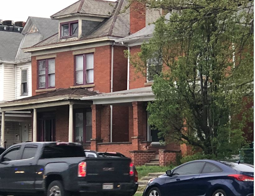 Warrants are served at the home with the purple trim around the windows during raids Tuesday in Huntington. (WCHS/WVAH)<p></p>