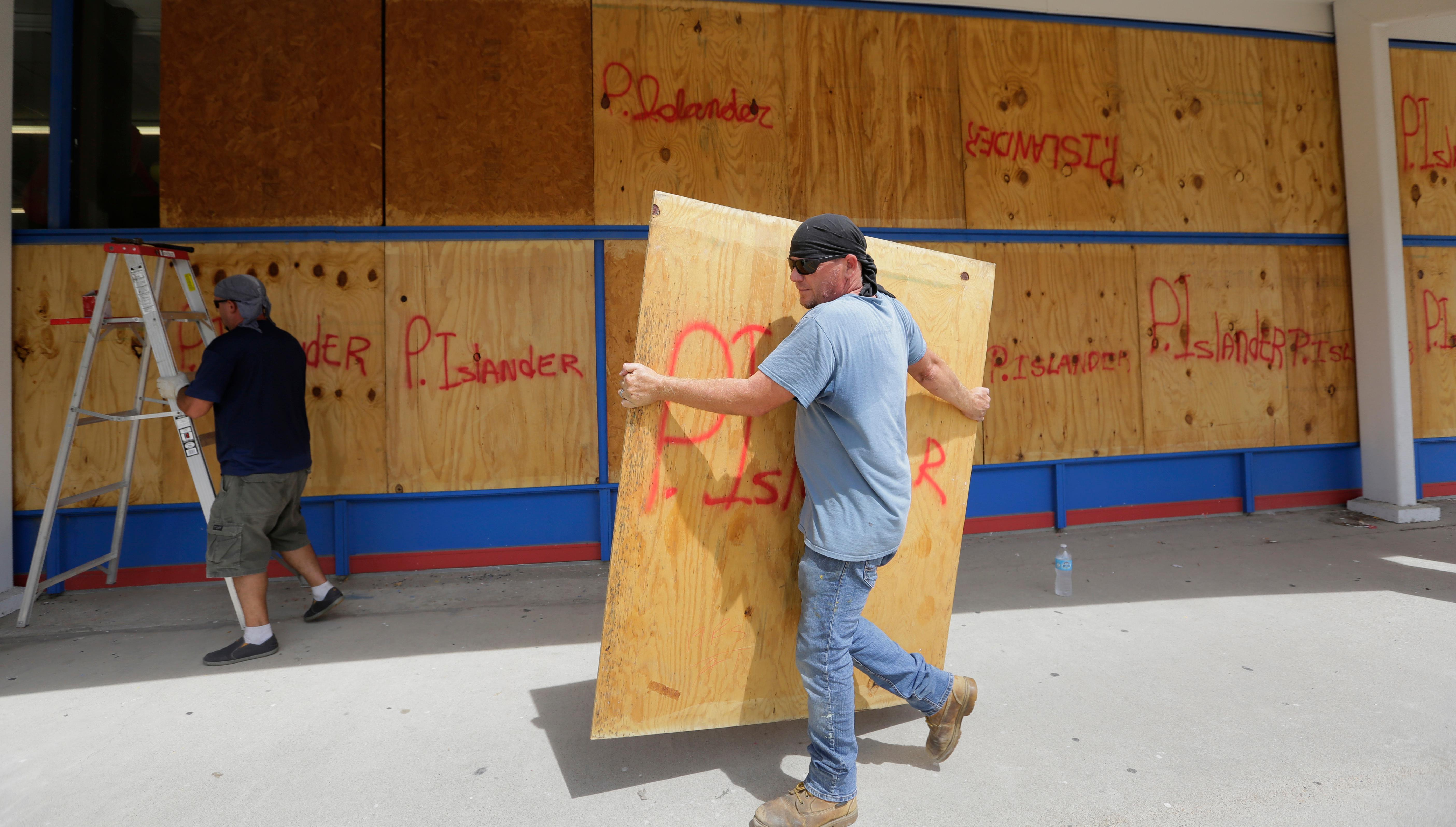 James Redford carries a sheet of plywood as he helps board up windows in preparation for Hurricane Harvey, Thursday, Aug. 24, 2017, in Corpus Christi, Texas. Two counties have ordered mandatory evacuations as Hurricane Harvey gathers strength as it drifts toward the Texas Gulf Coast.   (AP Photo/Eric Gay)