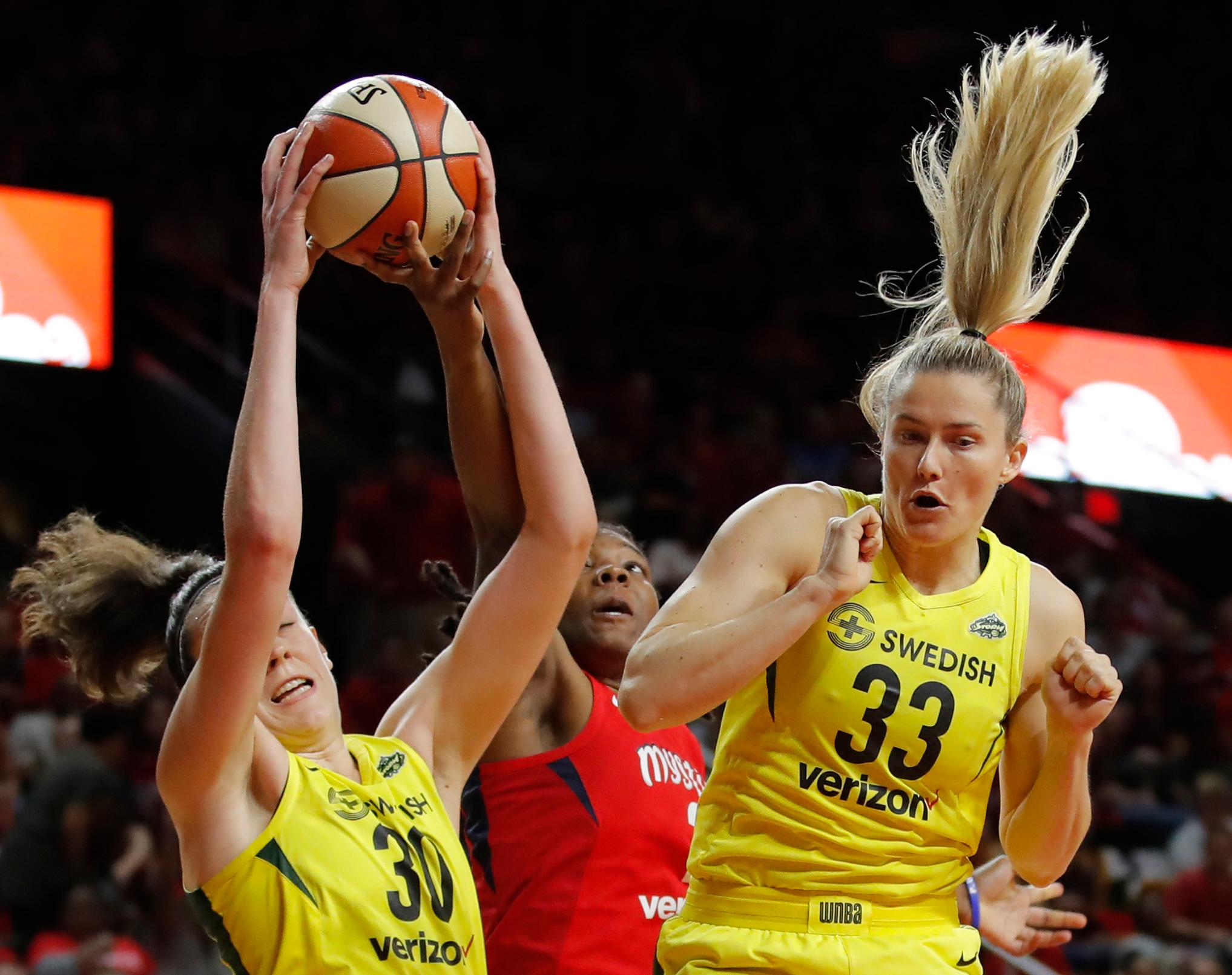 Seattle Storm forward Breanna Stewart (30) fights for control of the ball with Washington Mystics forward Myisha Hines-Allen (2) as Seattle Storm guard Sami Whitcomb (33) leaps at right during the first half of Game 3 of the WNBA basketball finals, Wednesday, Sept. 18 2018, in Fairfax, Va. (AP Photo/Carolyn Kaster)