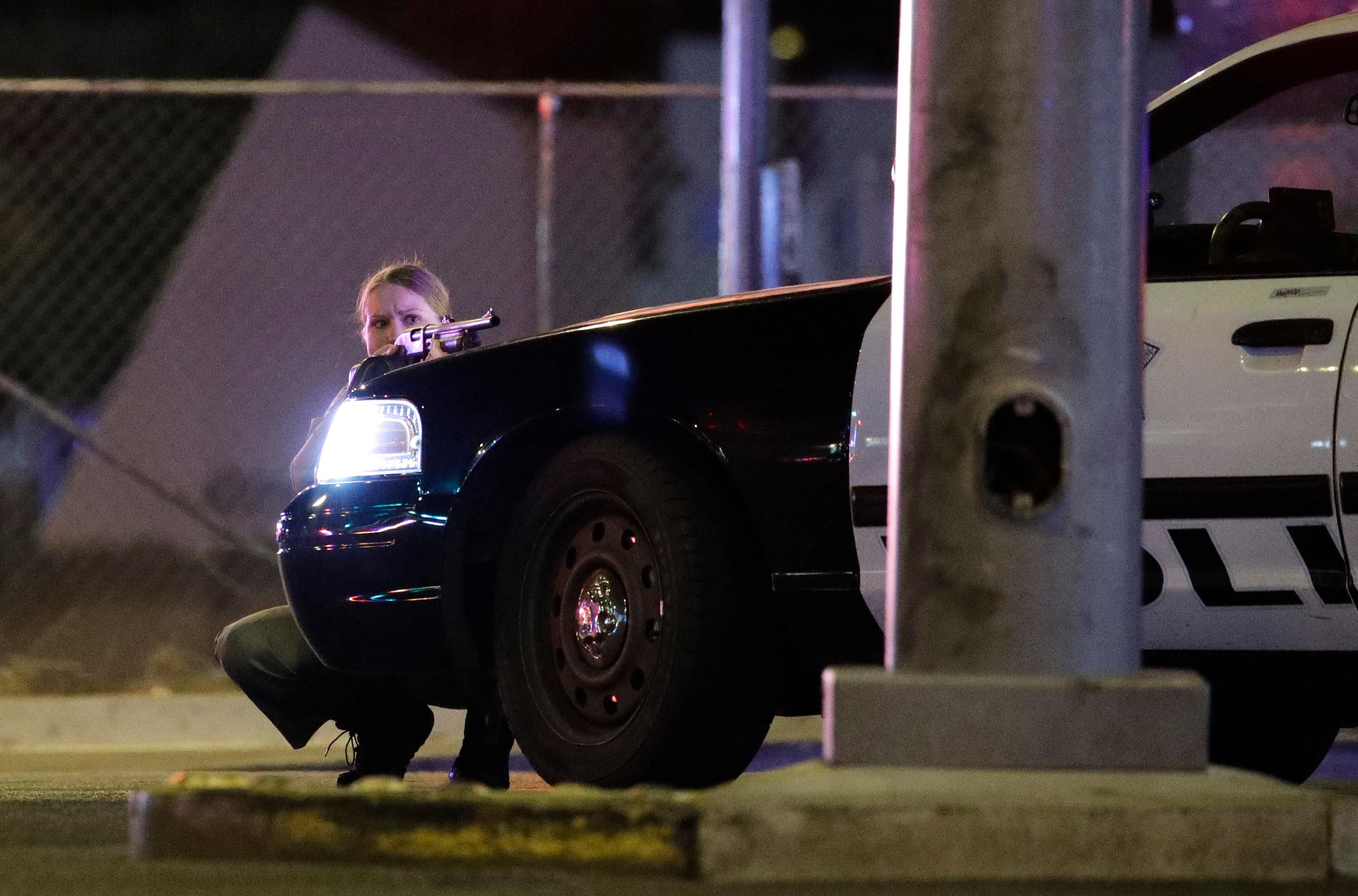 A police officer takes cover behind a police vehicle during a shooting near the Mandalay Bay resort and casino on the Las Vegas Strip, Sunday, Oct. 1, 2017, in Las Vegas. (AP PhotoJohn Locher).jpg