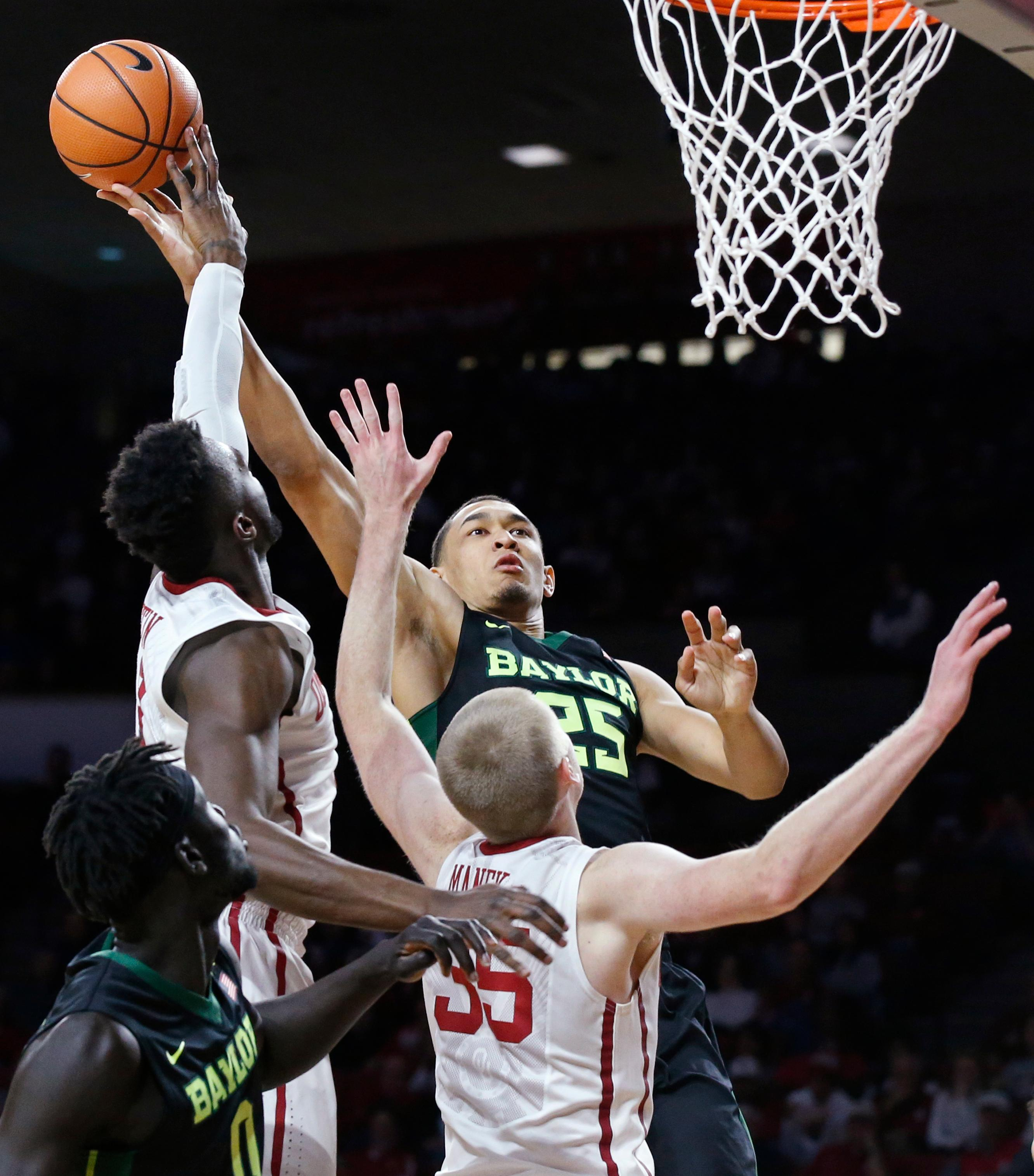 Baylor forward Tristan Clark (25) shoots as Oklahoma forward Khadeem Lattin, left, and forward Brady Manek (35) defend during the first half of an NCAA college basketball game in Norman, Okla., Tuesday, Jan. 30, 2018. (AP Photo/Sue Ogrocki)