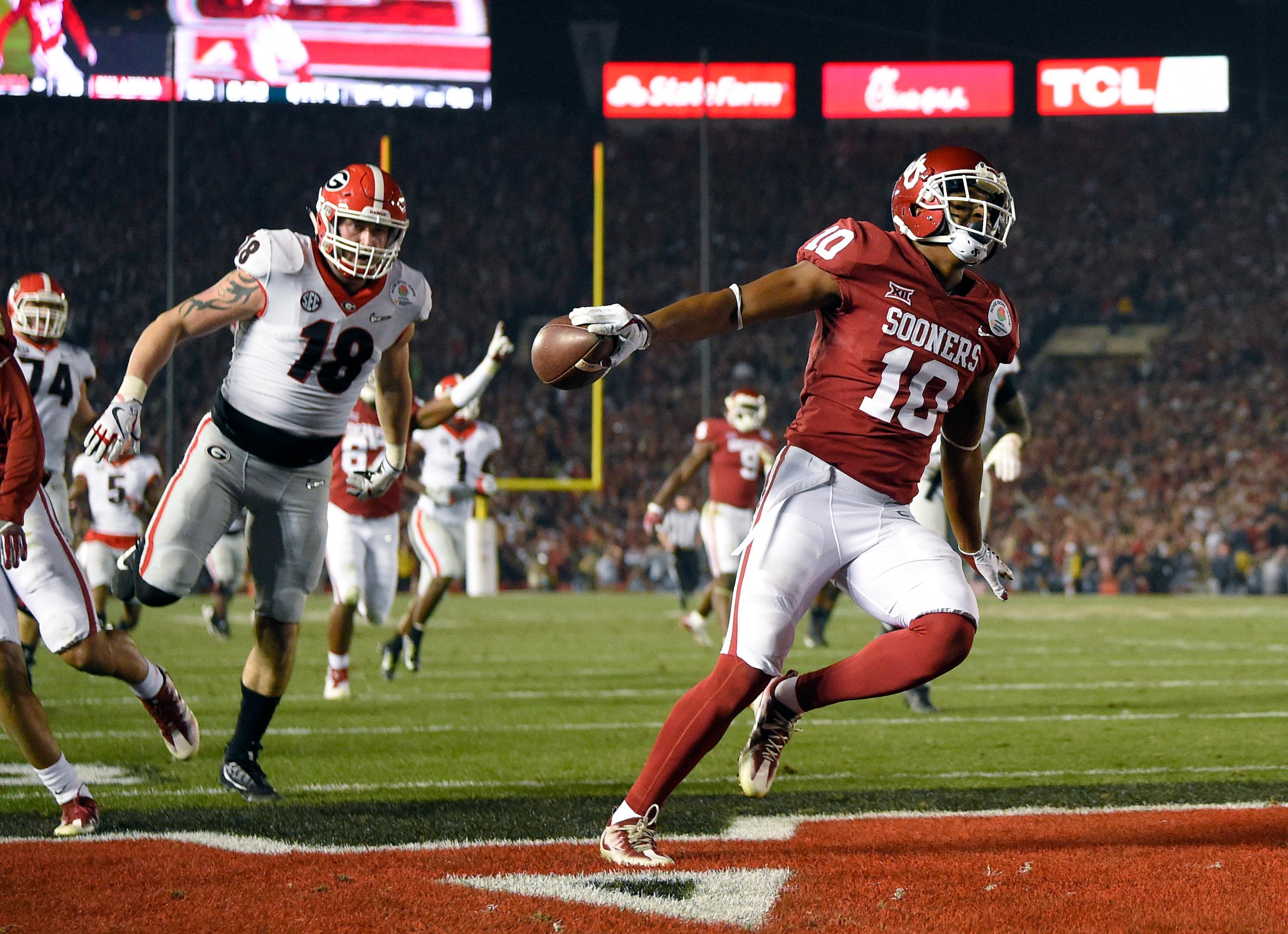 Oklahoma defensive back Steven Parker (10) scores a touchdown ahead of Georgia tight end Isaac Nauta (18) after Parker recovered a fumble during the second half of the Rose Bowl NCAA college football game Monday, Jan. 1, 2018, in Pasadena, Calif. (AP Photo/Mark J. Terrill)