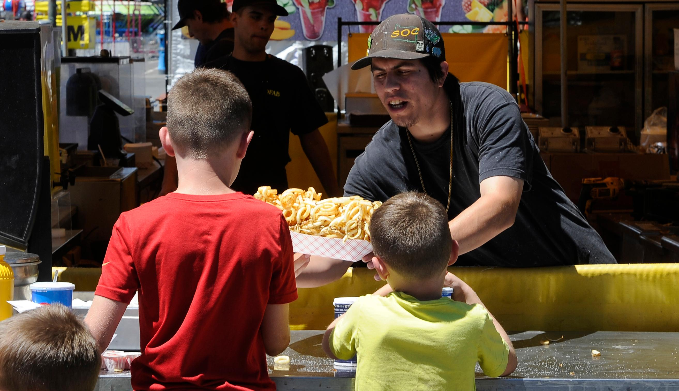 Andy Atkinson / Mail Tribune<br>Armando Barreto hands a basket of curly fries to kids at the Jackson County Fair Tuesday.