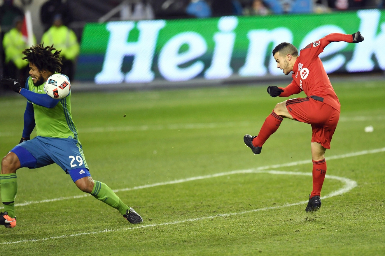 Toronto FC forward Sebastian Giovinco (10) hits Seattle Sounders defender Roman Torres (29) in the face as he shoots at the net during first-half MLS Cup final soccer action in Toronto, Saturday, Dec. 10, 2016. (Frank Gunn/The Canadian Press via AP)
