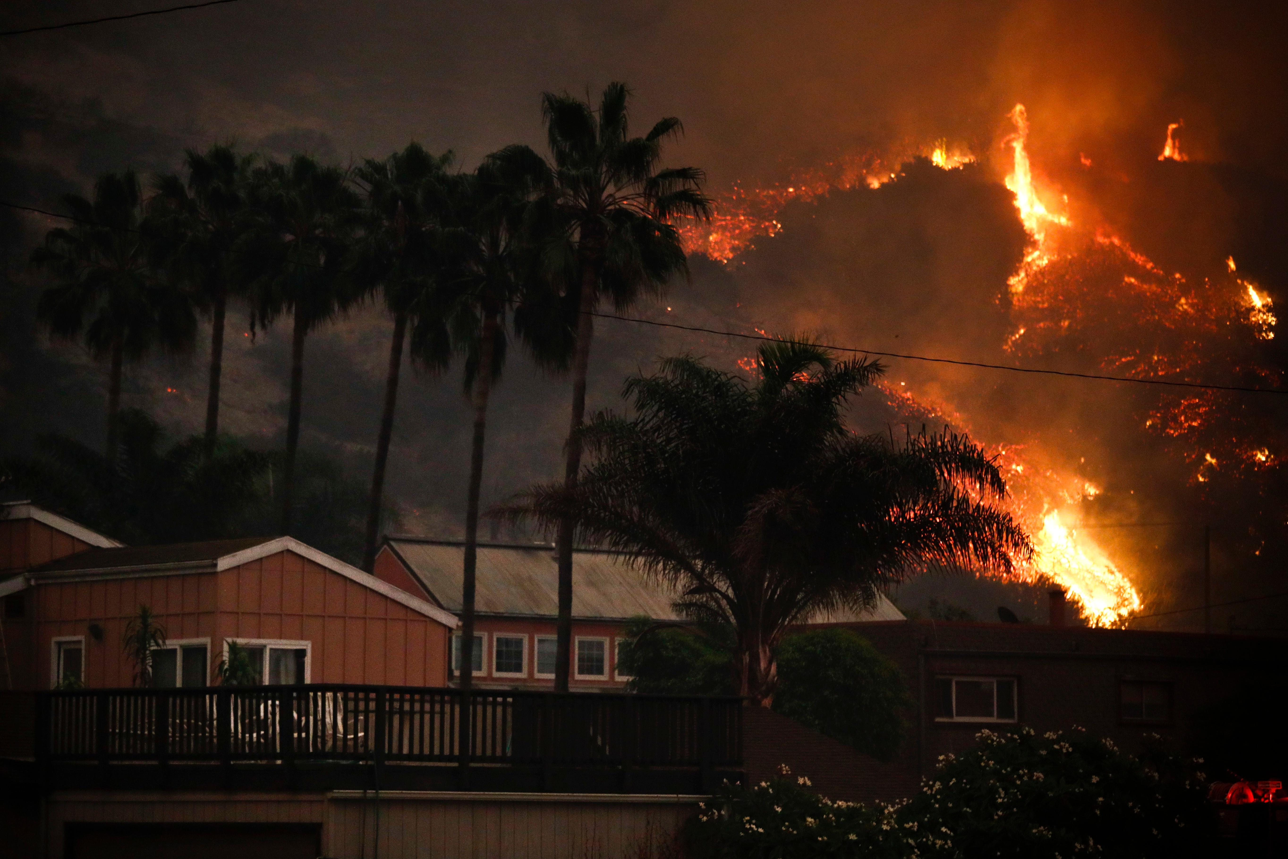 A wildfire threatens homes as it burns along a hillside in La Conchita, Calif., Thursday, Dec. 7, 2017. The wind-swept blazes have forced tens of thousands of evacuations and destroyed dozens of homes. (AP Photo/Jae C. Hong)