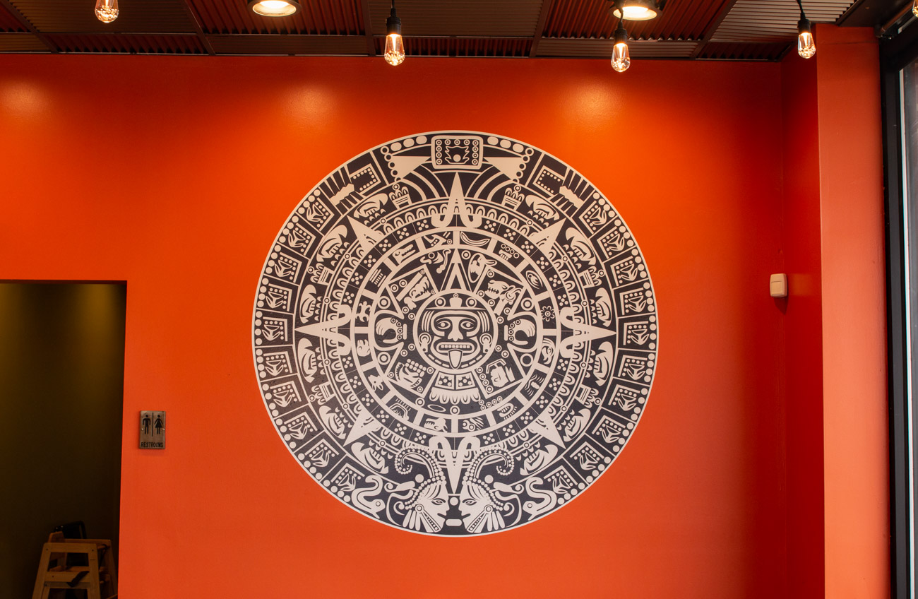"The inspiration for the funky, bright decor came from Mark. ""We wanted it to be modern with clean lines, but with some old flair like the Aztec calendar [and figures] that take you back,"" he says. Putting together the restaurant was truly a family affair, as Mark, Melanie, Mark's parents, and others worked together to build the benches, the bar, and the multicolored shiplap wall themselves. They also sewed their own upholstery, wired the lights, and hung the reflective ceiling tiles in a grid. / Image: Elizabeth Lowry // Published: 12.24.19"