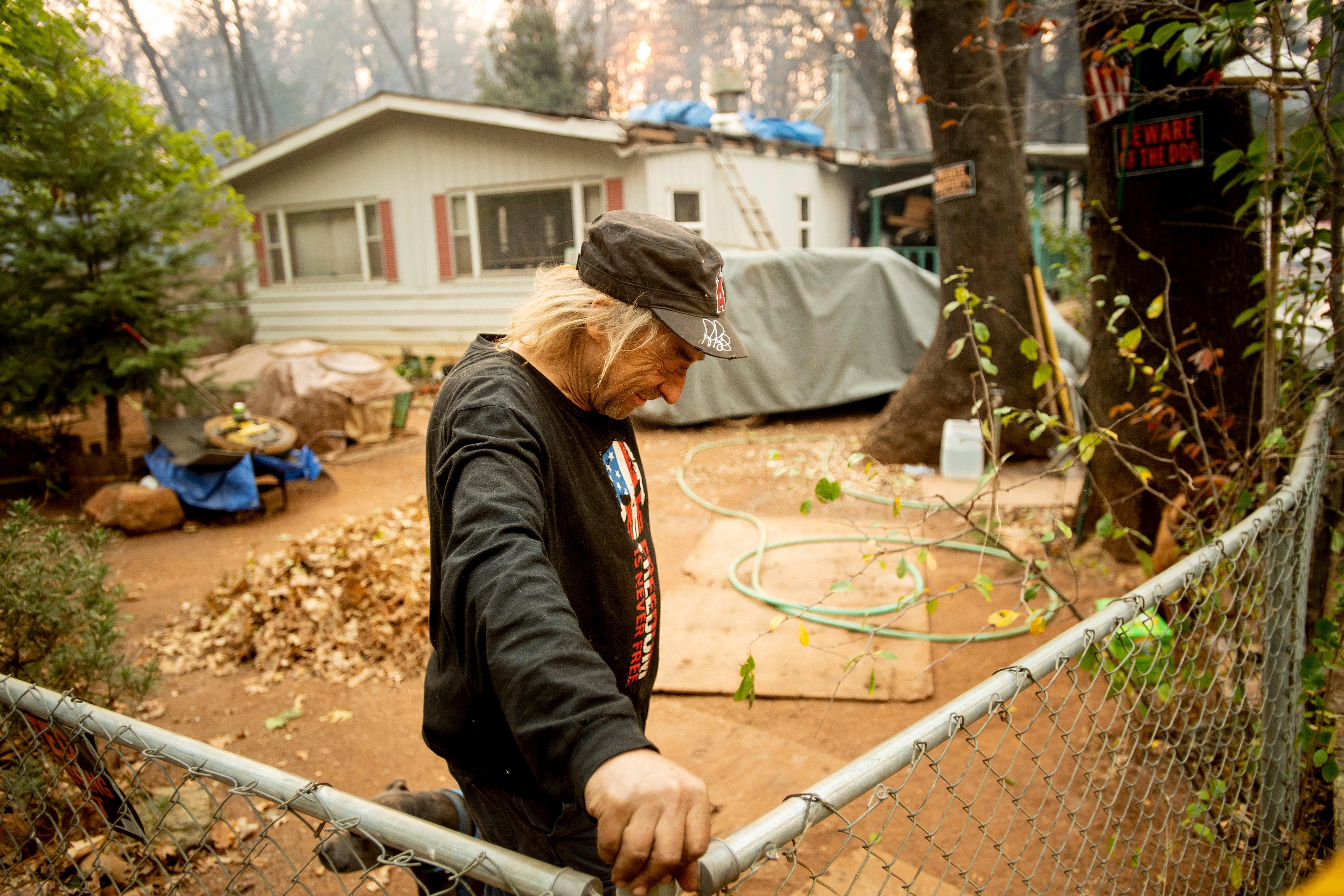 Jimmy Clements, who stayed at his home as the Camp Fire raged through Paradise, Calif., leans against his fence, Sunday, Nov. 11, 2018. Clements, whose home stands among destroyed residences, said he built an FM radio out of a potato and wire to keep up with news about the fire. (AP Photo/Noah Berger)