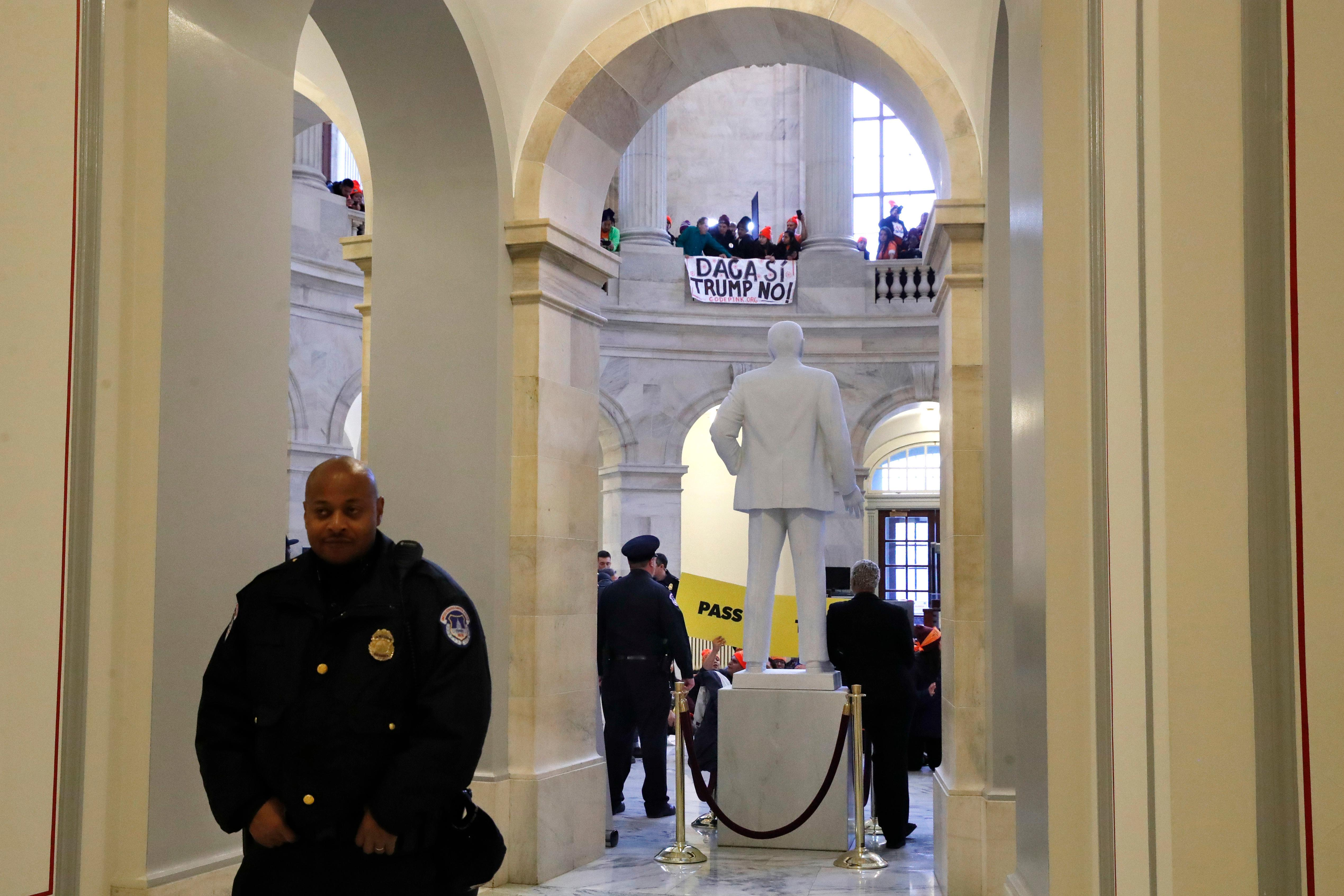 "With a sign hanging above that says ""DACA Si, Trump No,"" Capitol Police hold their posts as people participate in civil disobedience in support of the Deferred Action for Childhood Arrivals (DACA) program, in the Russell Rotunda, Wednesday, Feb. 7, 2018, on Capitol Hill in Washington. (AP Photo/Jacquelyn Martin)"