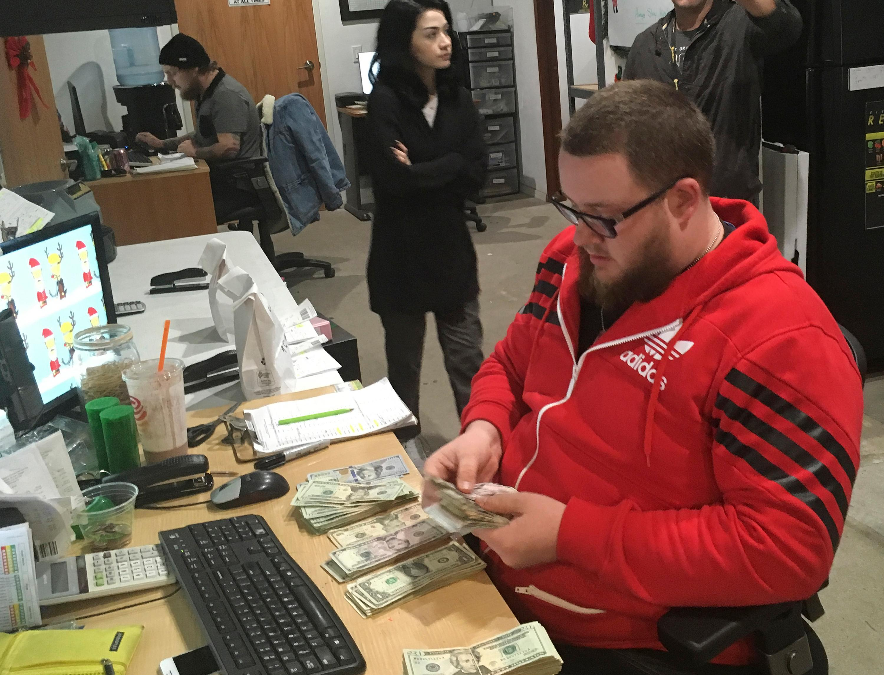 In this Wednesday, Dec. 27, 2017, photo Employee Joshua Wilson counts cash at the Golden State Greens marijuana dispensary in San Diego. A few dozen California shops have cleared a final hurdle to sell marijuana for recreational use starting Monday, Jan. 1, 2018, and regulators will work through the weekend to grant more licenses. (AP Photo/Elliot Spagat)
