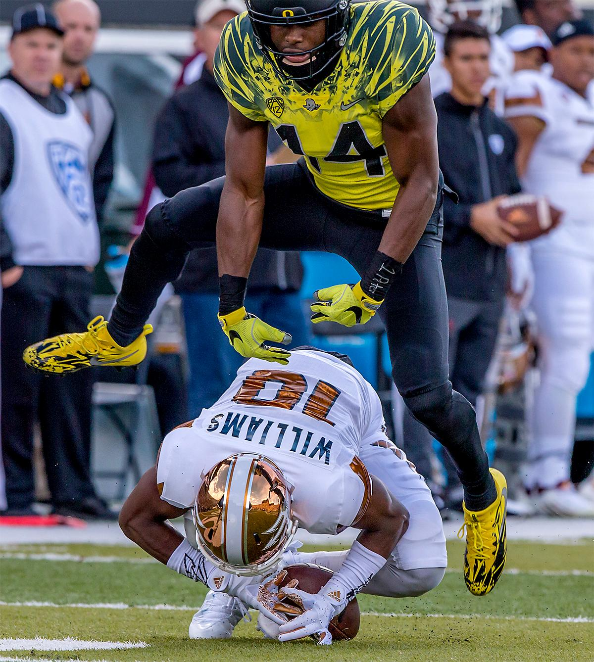 The Duck's Ugo Amadi (#14) jumps over the Sun Devils' Kyle Williams (#10) as Williams makes a catch. The Oregon Ducks broke their losing streak by defeating the ASU Sun Devils on Saturday 54-35. Photo by August Frank, Oregon News Lab