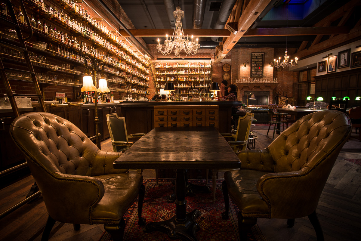 The Multnomah Whiskey Library though is on another level entirely - vast shelves of booze accessed by bartenders swinging from library ladders as they craft personalized flights of whiskey or other liquors accompanied by excellent snacks (Image: Dina Avila Photography)