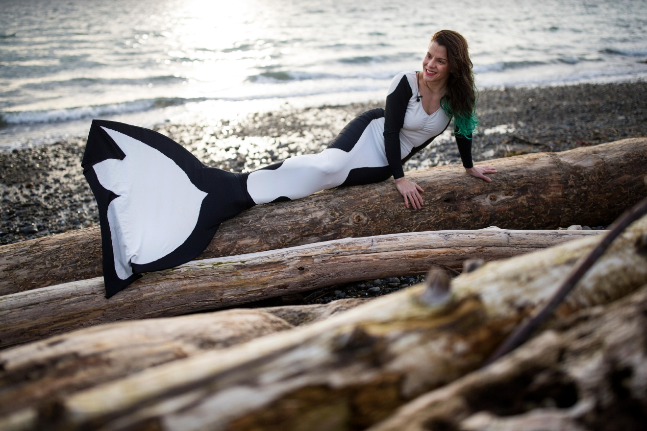 Jamie Von Stratton, founder of the Seattle Mermaids, lays out on some driftwood during an interview with Seattle Refined at Charles Richey Sr. Viewpoint. (Sy Bean / Seattle Refined)