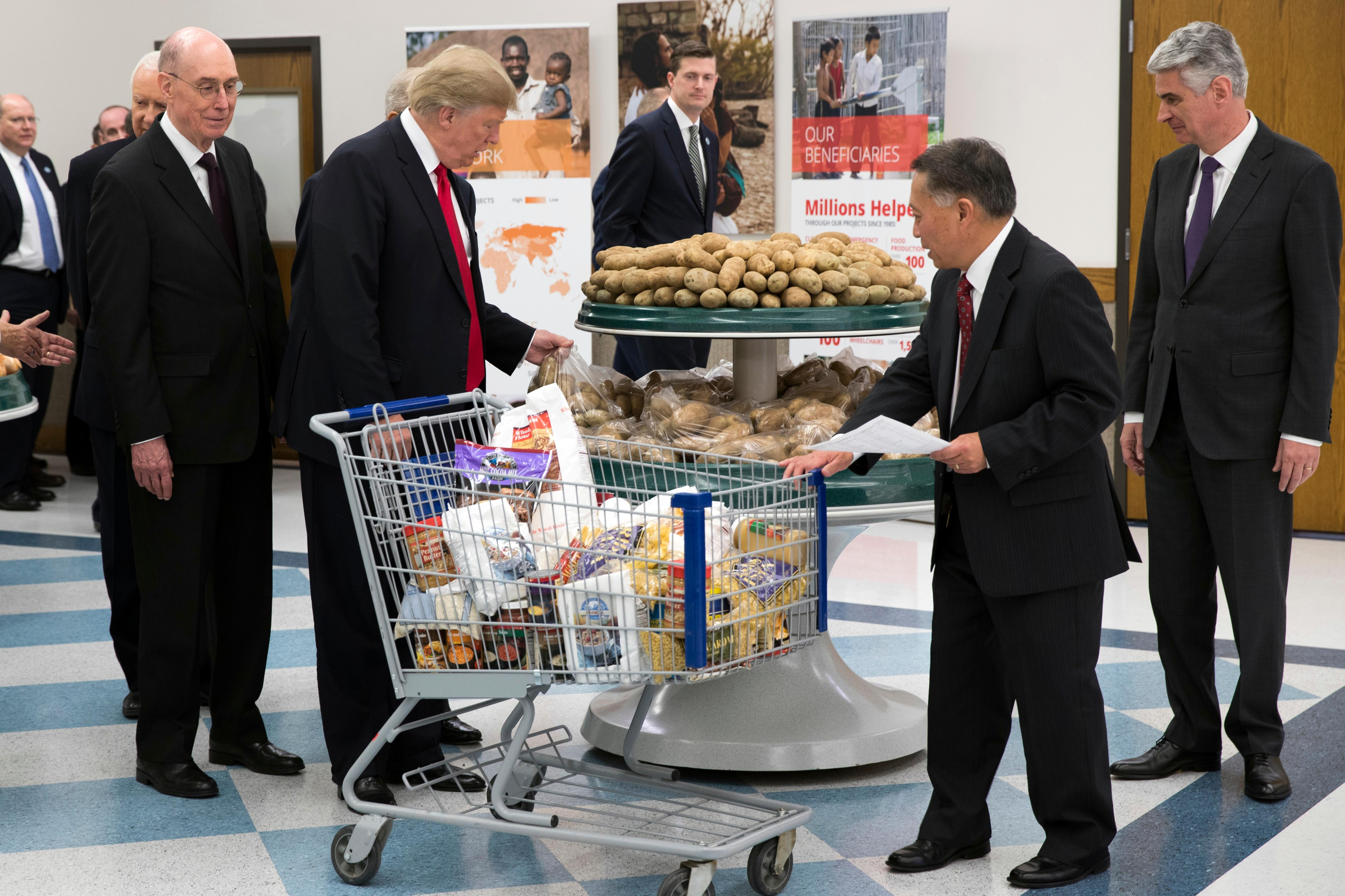 President Donald Trump lifts a bag of potatoes as he  tours the Church of Jesus Christ of Latter-Day Saints Welfare Square food distribution center, Monday, Dec. 4, 2017, in Salt Lake City. (AP Photo/Evan Vucci)