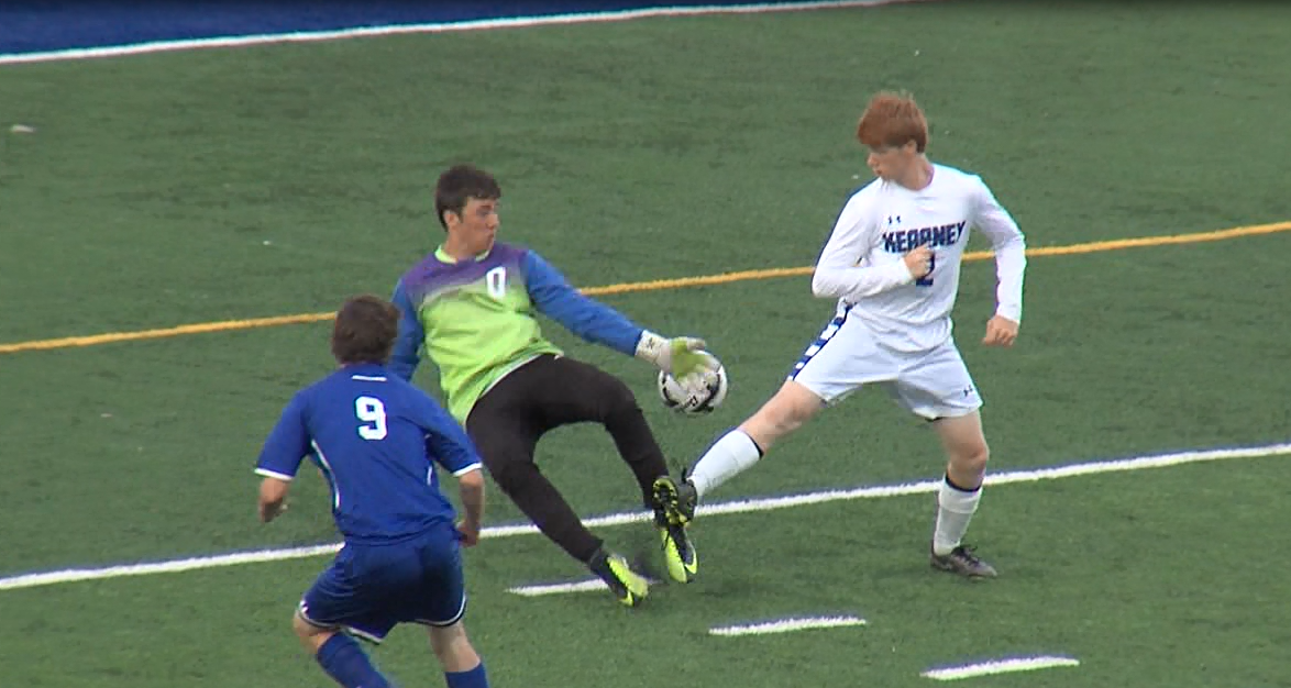 North Platte junior Joshua Cauffman (9) splits a Kearney defender and goalie Jacob Hardy during a game at Kearney High School on April 18, 2017 (NTV News)