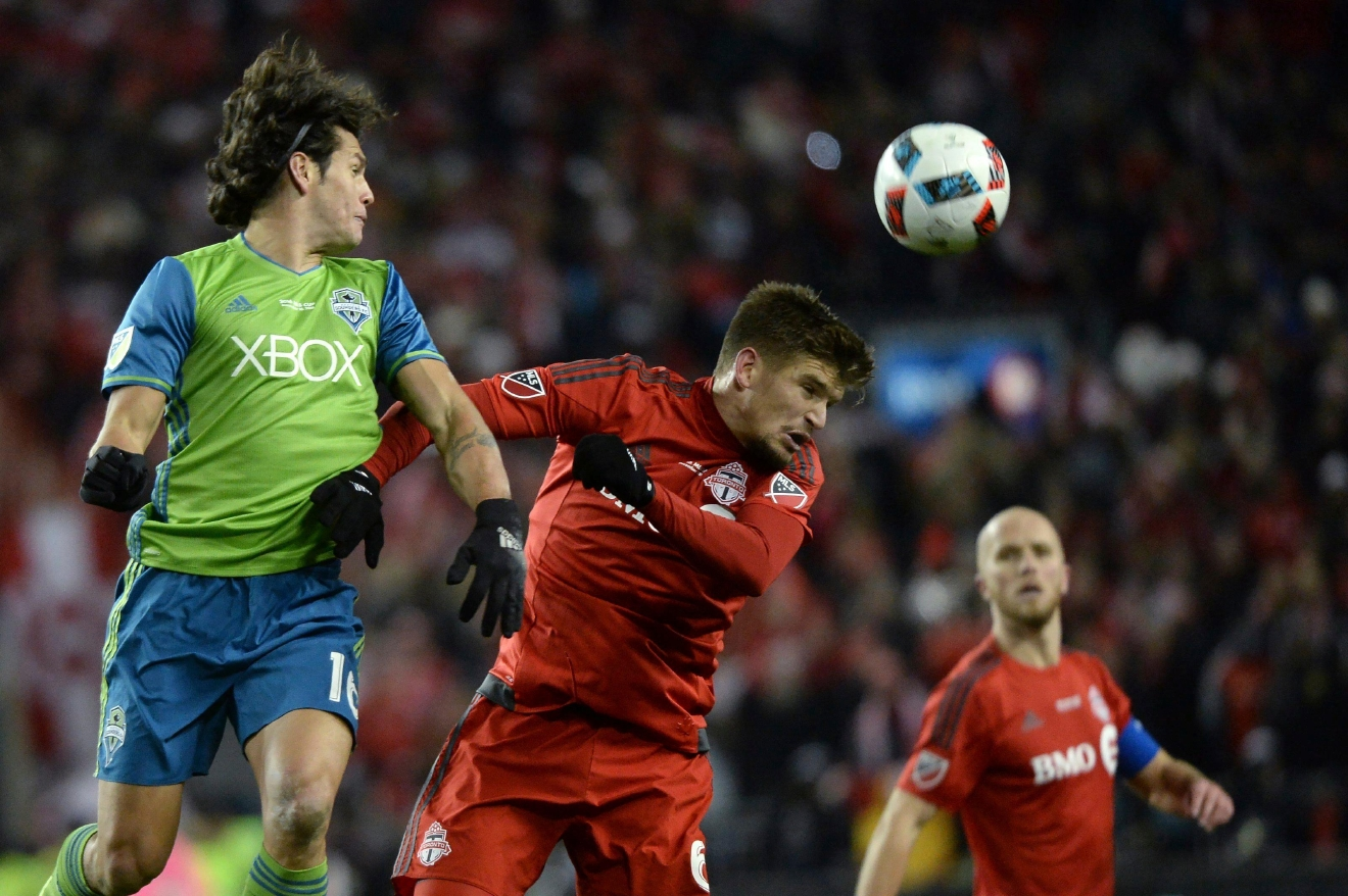 Seattle Sounders forward Nelson Valdez, left, and Toronto FC defender Nick Hagglund, center, battle for the ball as Toronto's Michael Bradley, right, looks on during first-half MLS Cup final soccer action in Toronto, Saturday, Dec. 10, 2016. (Nathan Denette/The Canadian Press via AP)