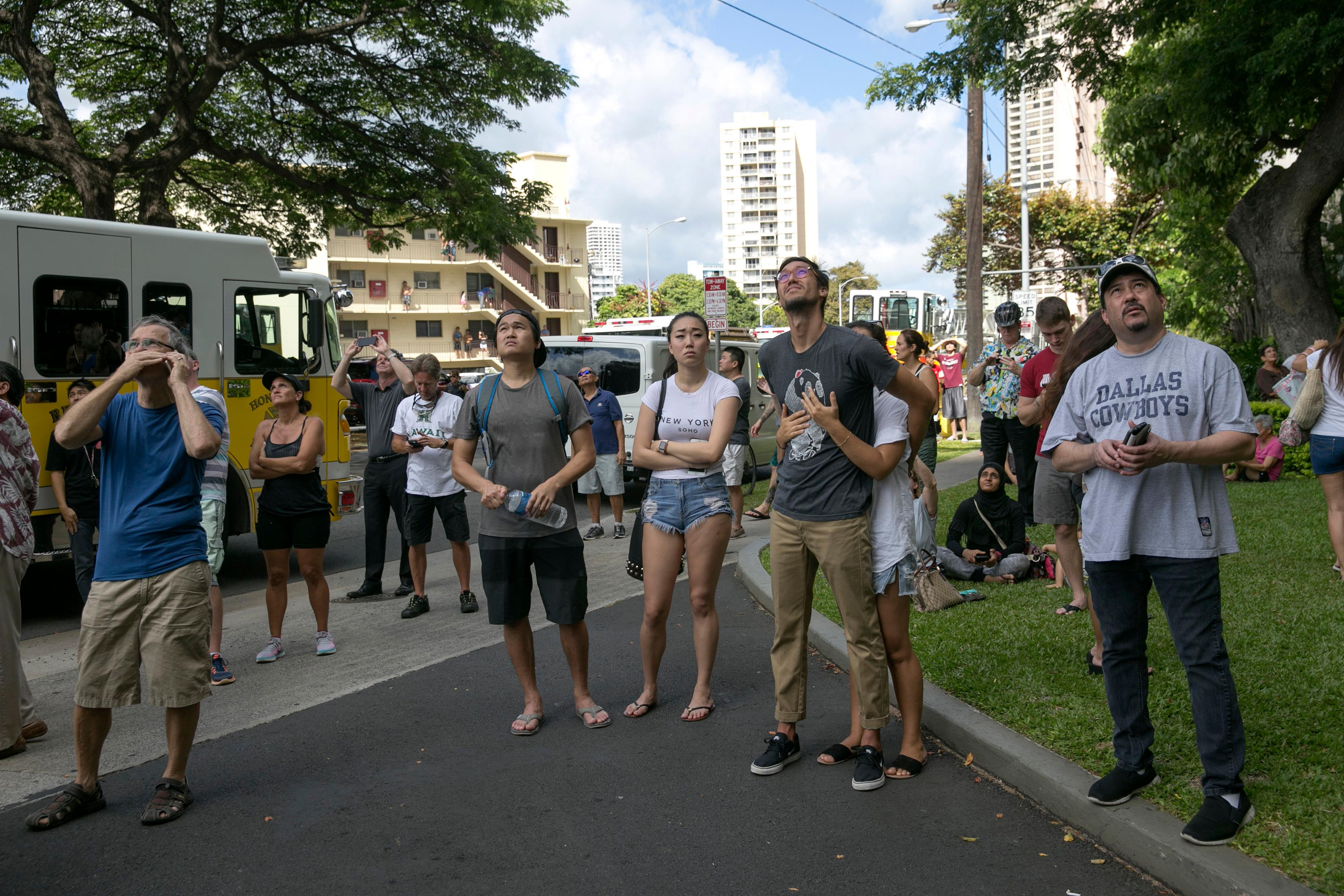 Crowds gather to watch a fire burn at the Marco Polo apartment complex, Friday, July 14, 2017, in Honolulu. (AP Photo/Marco Garcia)