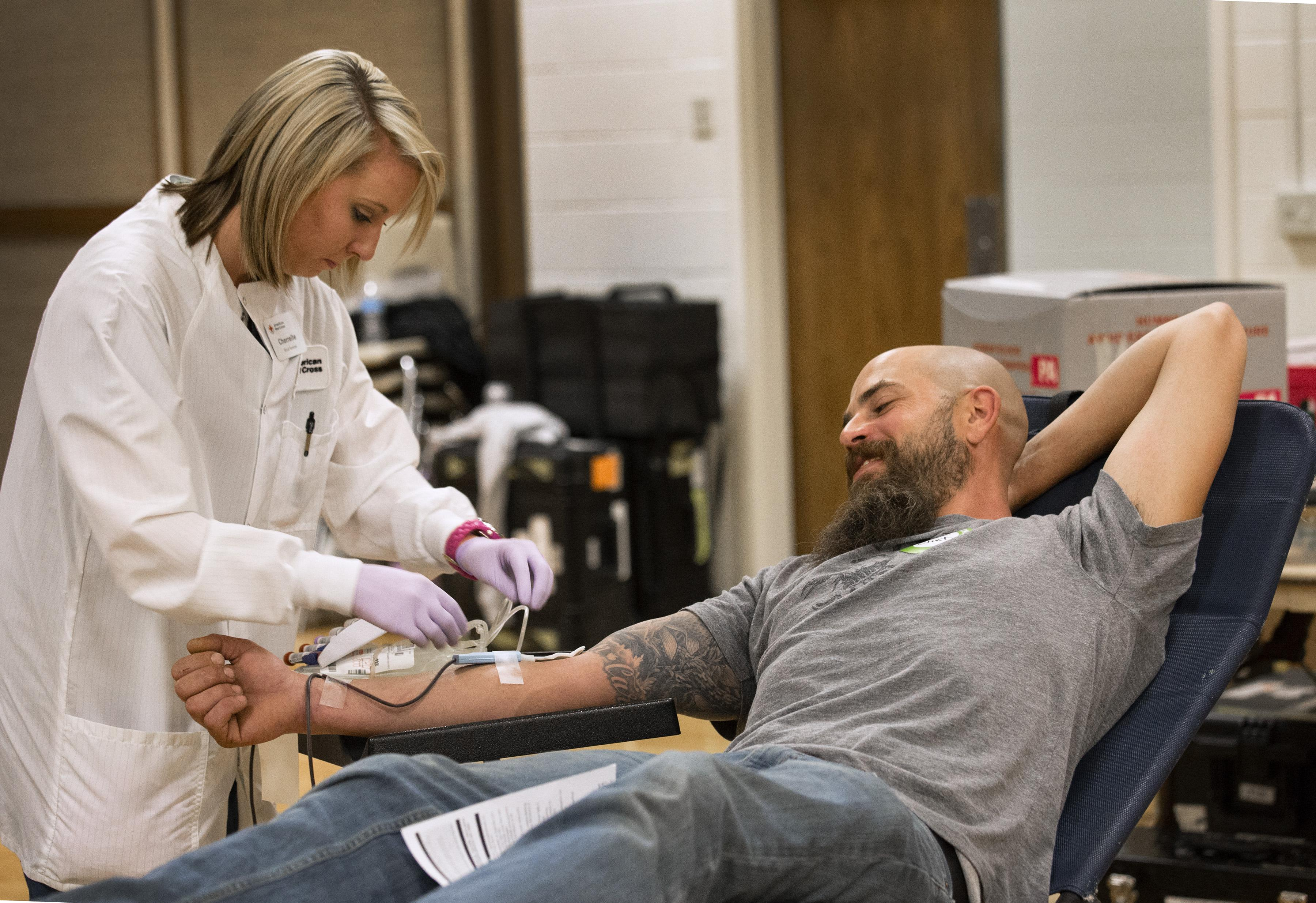 May 14, 2014. Murray, Utah. American Red Cross collections staff member Cherrelle Simon collects a blood donation from Clint Kraft.  Clint says that he gives blood because his wife suffers from a rare disease. Photo by Amanda Romney/American Red Cross