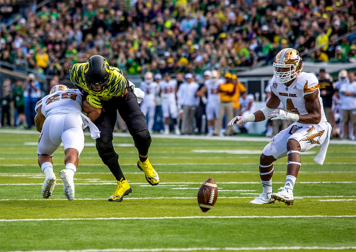 The Sun Devils' Viliami Laiu Moeakiola (#28) collides with the Duck's Pharaoh Brown (#85) as the ball rolls across the field. Oregon lead at the end of the 1st half 30-14. Photos by August Frank, Oregon News Lab