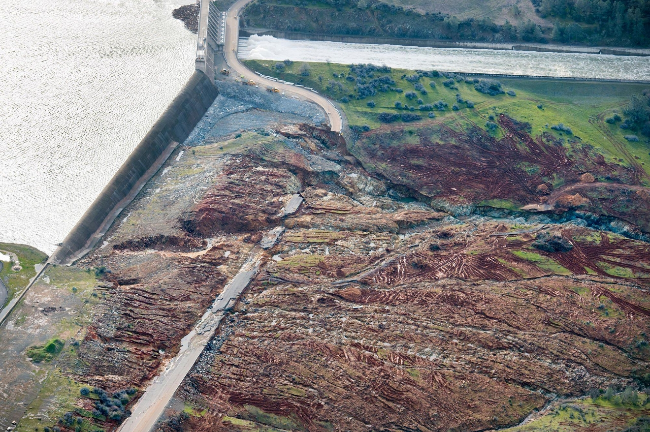 In an aerial photo, the emergency spillway at Lake Oroville shows signs of damage from the water which spilled over recently, on Monday, Feb. 13, 2017, in Oroville, Calif. Sunday afternoon's evacuation order came after engineers spotted a hole on the concrete lip of the secondary spillway for the 770-foot-tall Oroville Dam and told authorities that it could fail within the hour. The water level dropped Monday behind the nation's tallest dam, reducing the risk of a catastrophic spillway collapse and easing fears that prompted the evacuation of nearly 200,000 people downstream.    (Randy Pench/The Sacramento Bee via AP)