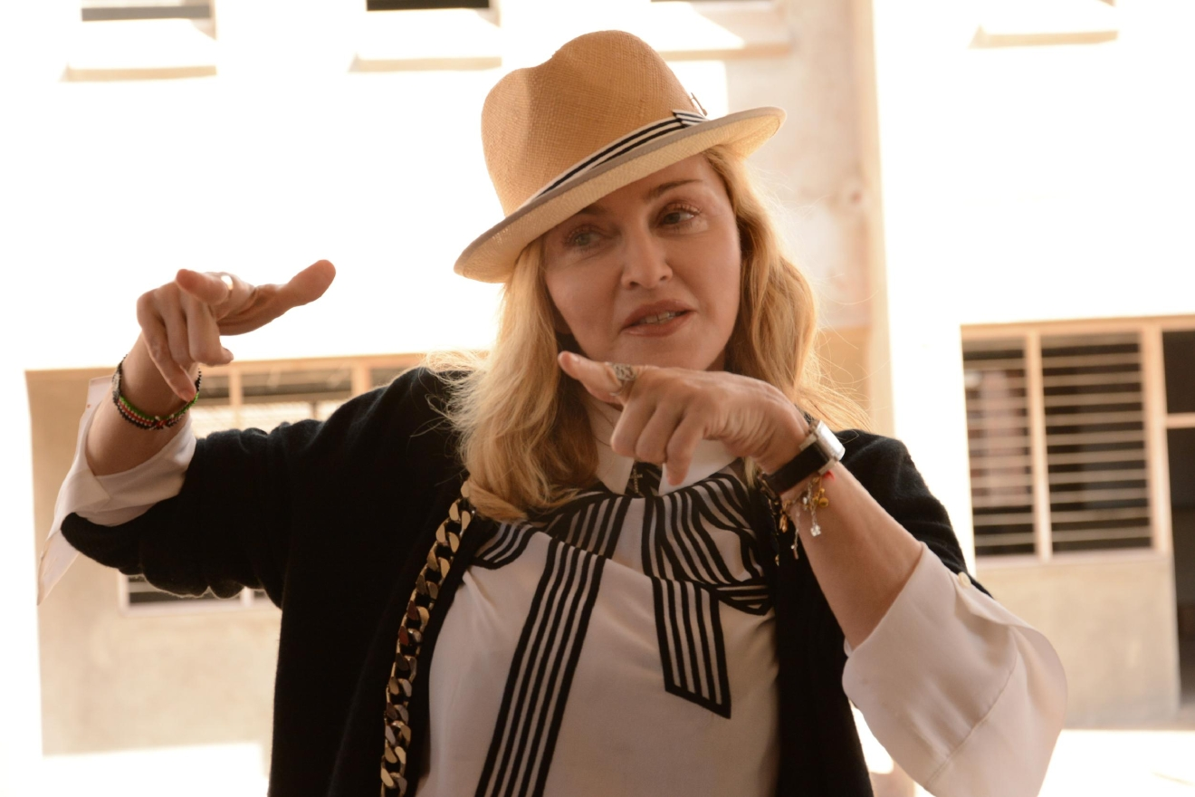 US performer Madonna gestures after visiting the paediatric surgery and Malawi's first ever intensive care unit under construction, at Queen Elizabeth Central Hospital in the southern city of Blantyre, Sunday, July 10, 2016. The pop star has been in Malawi for a week during which she has met with President Peter Mutharika and health minister Peter Kumpalume. Madonna, who has adopted two children from Malawi, is scheduled to visit Queen Elizabeth Central Hospital on Sunday to view the pediatric unit where construction started in May 2015 and which is expected to open in early 2017.  (AP Photo/Thoko Chikondi)