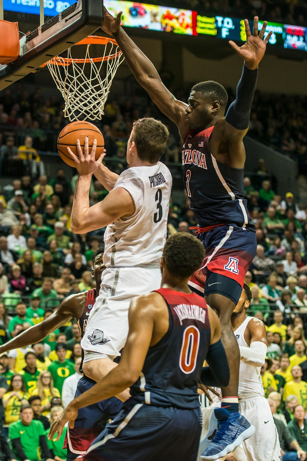 Oregon's Payton Pritchard (3) goes up for a layup against Arizona's Rawle Alkins (1) in theor matchup at Matthew Knight Arena Saturday. The Ducks upset the fourteenth ranked Wildcats 98-93 in a stunning overtime win in front of a packed house of over 12,000 fans for their final home game to improve to a 19-10 (9-7 PAC-12) record on the season. Oregon will finish out regular season play on the road in Washington next week against Washington State on Thursday, then Washington on the following Saturday. (Photo by Colin Houck)