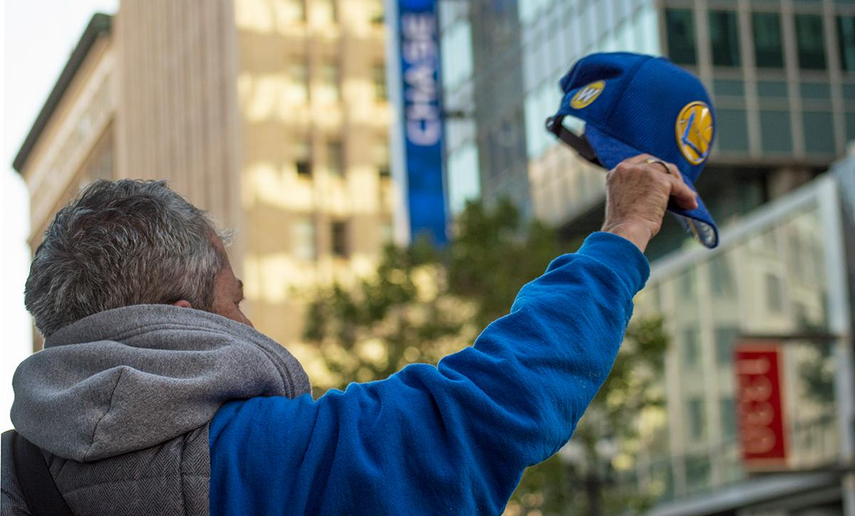A fan cheers, holding his Golden State Warriors hat up to the sky. Photo by Emily Gonzalez, Oregon News Lab.