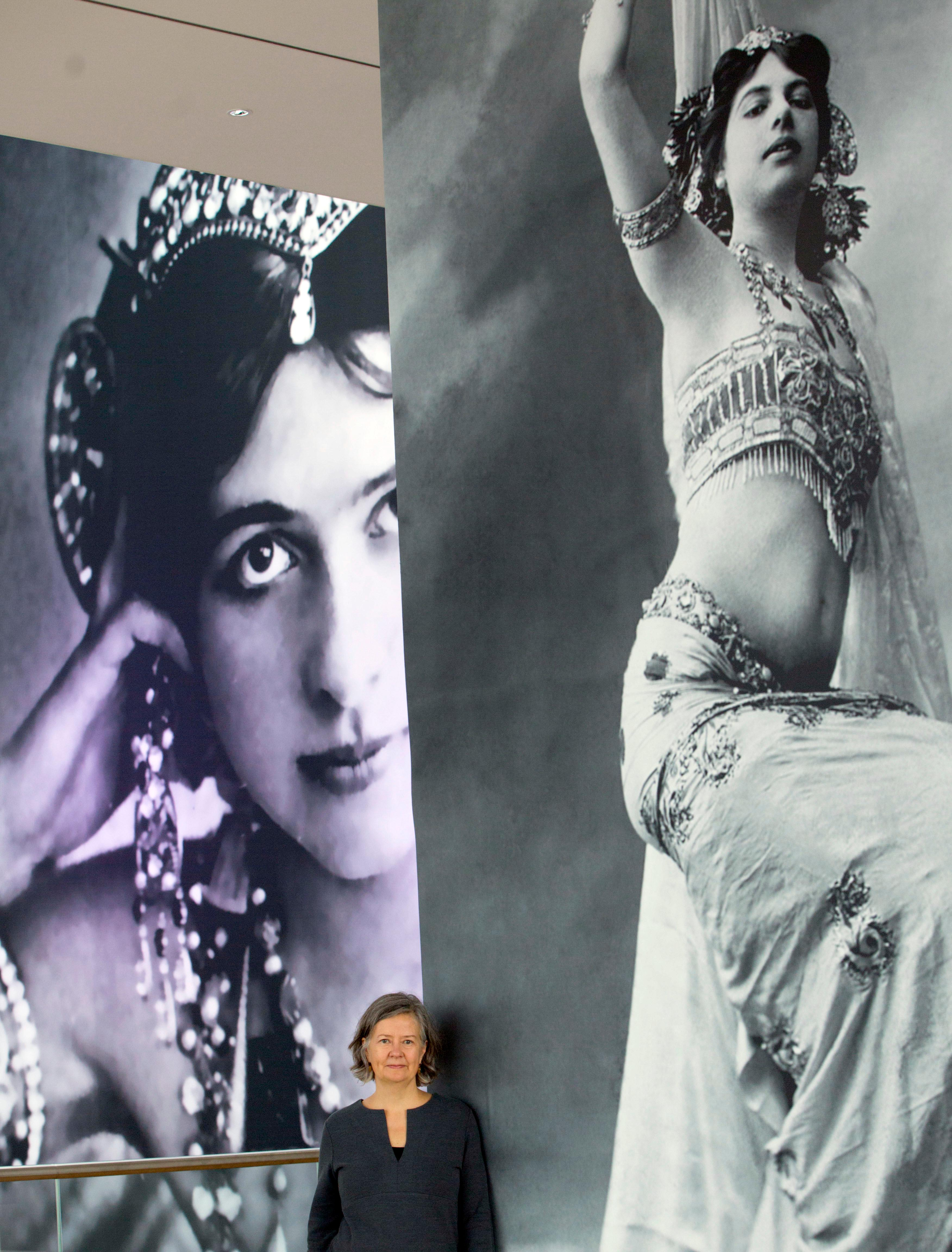 In this photo taken on Friday, Oct. 13, 2017, historian Julie Wheelright poses next to a giant poster of Margaretha Zelle, also known as Mata Hari, at the Fries Museum in Leeuwarden, Netherlands. A century ago, on Oct. 15, 1917, an exotic dancer named Mata Hari was executed by a French firing squad, condemned as a sultry Dutch double agent who supposedly led tens of thousands of soldiers to their death during World War I. (AP Photo/Virginia Mayo)