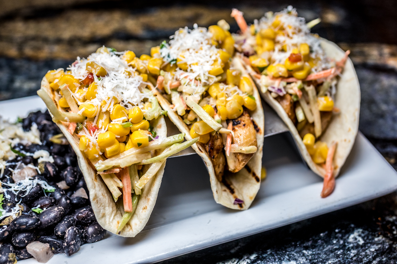 Chicken Tacos: three tacos stuffed with chicken, fire-roasted corn salsa, shredded cabbage, cotija cheese, and chipotle dressing served with a side of black beans and rice / Image: Catherine Viox{ }// Published: 3.7.20