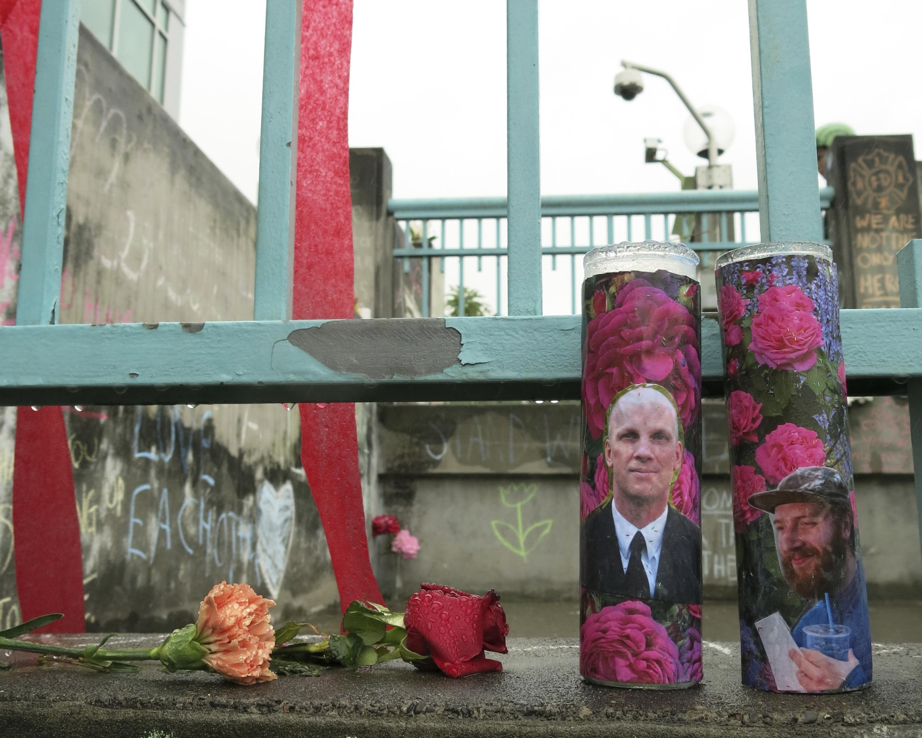Votive candles bearing the photos of Ricky Best, 53, and Taliesin Myrddin Namkai-Meche, 23, who grew up in Ashland, sit on a rain-soaked memorial on Tuesday in Portland. T[AP Photo/Gillian Flaccus]
