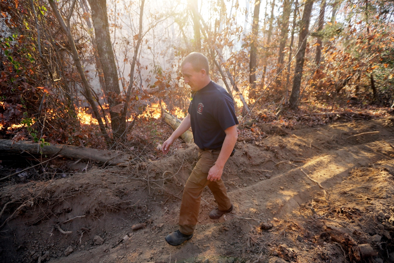 Assistant Chief Brent Masey, of the Highway 58 Fire Department in Harrison, Tenn., walks along a firebreak as he keeps watch on a wildfire Thursday, Nov. 10, 2016, in Soddy-Daisy, Tenn. Federal authorities say warmer-than-average temperatures and no rainfall are deepening a drought that's sparking forest fires across the Southeastern U.S. (AP Photo/Mark Humphrey)