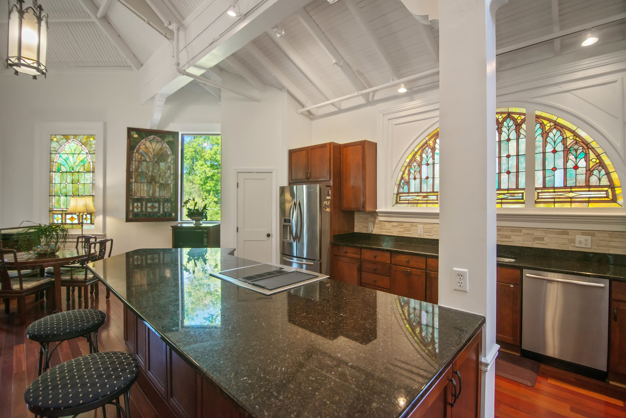 "From an elite girls' school to a medical facility, a chapel, a concert hall and now a two-bedroom/two-bathroom 3,500-square-foot house on the market for more than $1 million, this home has had quite the history! According to the current owners, this Silver Spring home ""is the crown jewel of the restored National Park Seminary,"" which operated as a private girls' school from 1894 to 1942 for the likes of girls with last names like Hershey, Chrysler, Heinz, Kraft and Maytag. When Walter Reed Army Hospital acquired the property in 1942, it became a medical facility for injured soldiers returning from World War II and the Korean War. Eventually the seminary was listed on the National Register of Historic Places and used as a chapel until the late 1980s when it fell into disrepair until the Alexander Company purchased the land in 2003 and decided to turn many of the buildings into luxury homes. Now the is stucco and wood exteriors combined with the 33 extant stained glass windows, abundance of natural light, 33' ceilings and rounded walls give the place a very ""Guggenheimish"" aesthetic. (Image: Courtesy{ }Houwzer Realty)"