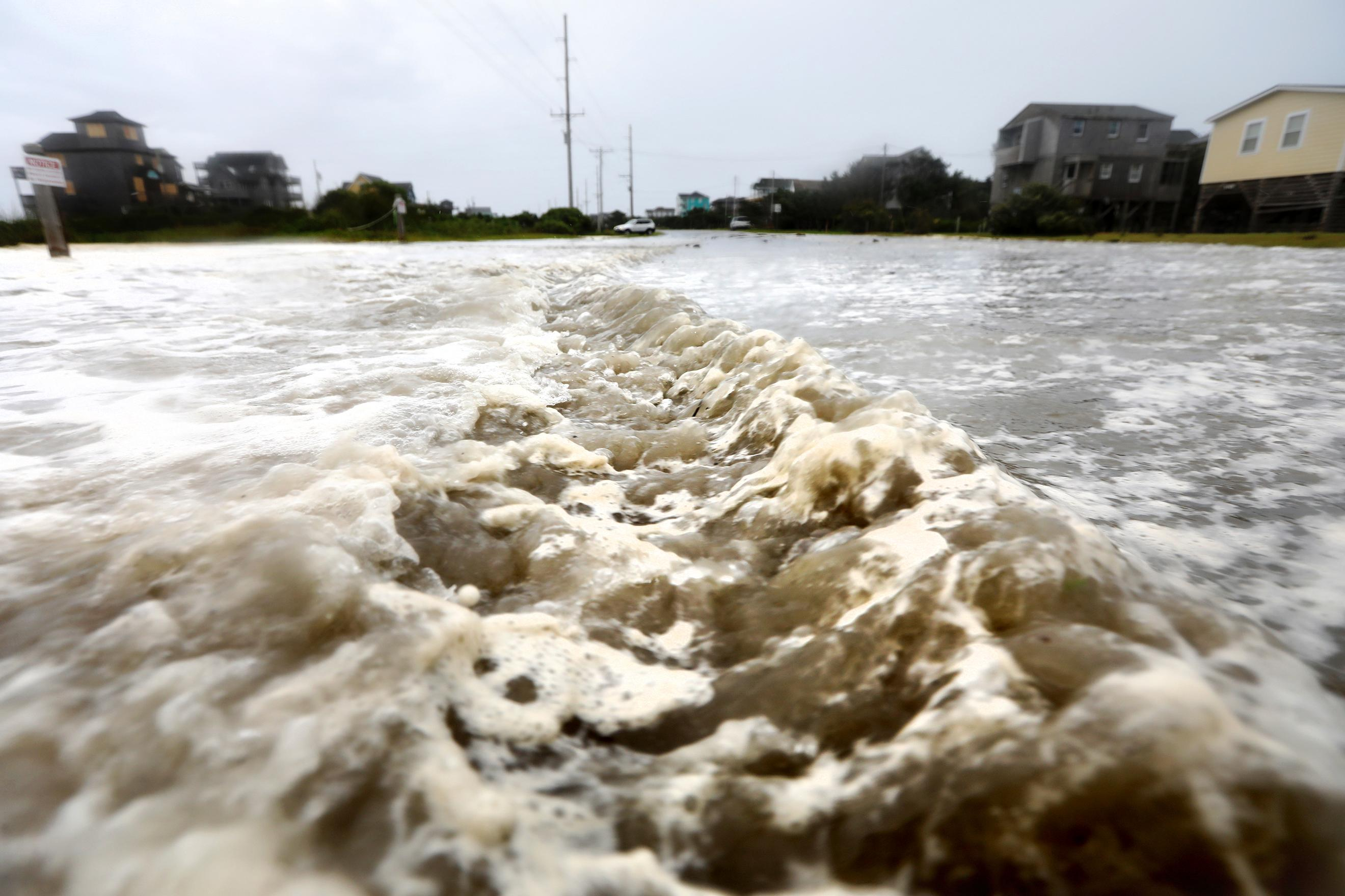 Ocean waters rushes down Hwy 12 in Frisco, N.C., on Hatteras Island as the effects of Hurricane Florence breach the dune line on Thursday, Sept. 13, 2018.  (Steve Earley /The Virginian-Pilot via AP)