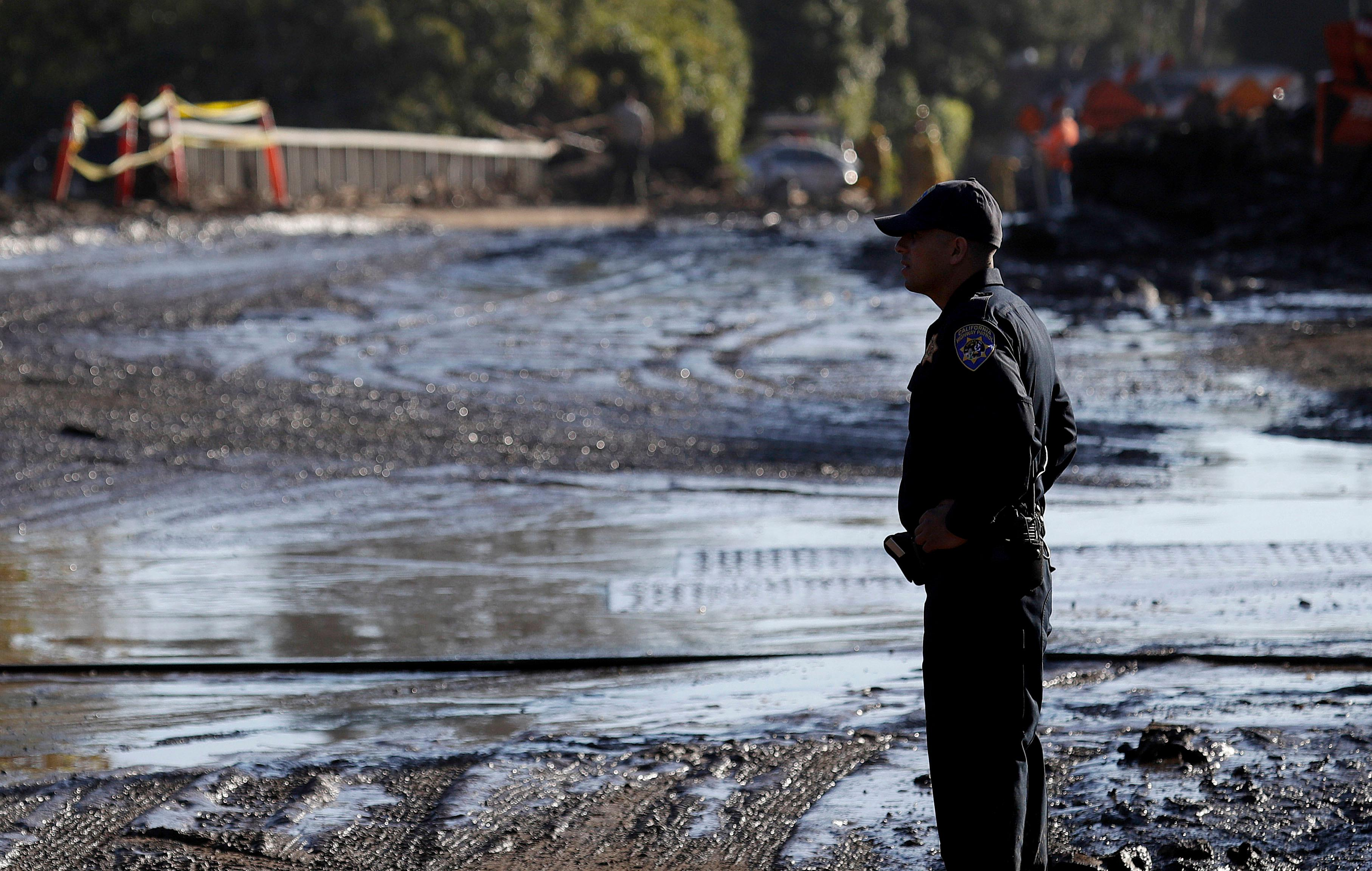 A California Highway Patrol officer stands in front of a road damaged from storms in Montecito, Calif., Thursday, Jan. 11, 2018. Rescue workers slogged through knee-deep ooze and used long poles to probe for bodies Thursday as the search dragged on for victims of the mudslides that slammed this wealthy coastal town. (AP Photo/Marcio Jose Sanchez)