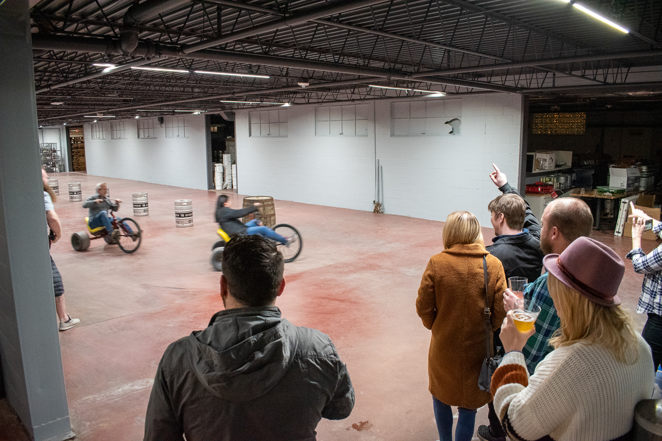 Big wheel racing stole the show as guests spilled into a back bay of the large distillery to cheer on friends. / Image: Matt Groves // Published: 12.8.19