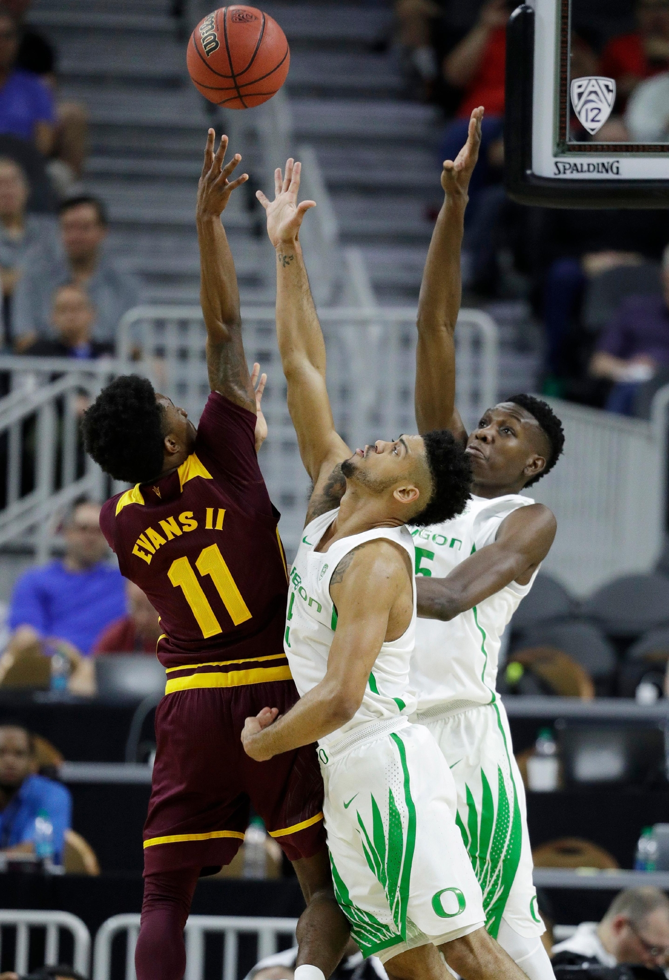 Oregon's Chris Boucher, right, and Oregon's Tyler Dorsey, center, try to block a shot by Arizona State's Shannon Evans II during the first half of an NCAA college basketball game in the quarterfinals of the Pac-12 men's tournament Thursday, March 9, 2017, in Las Vegas. (AP Photo/John Locher)