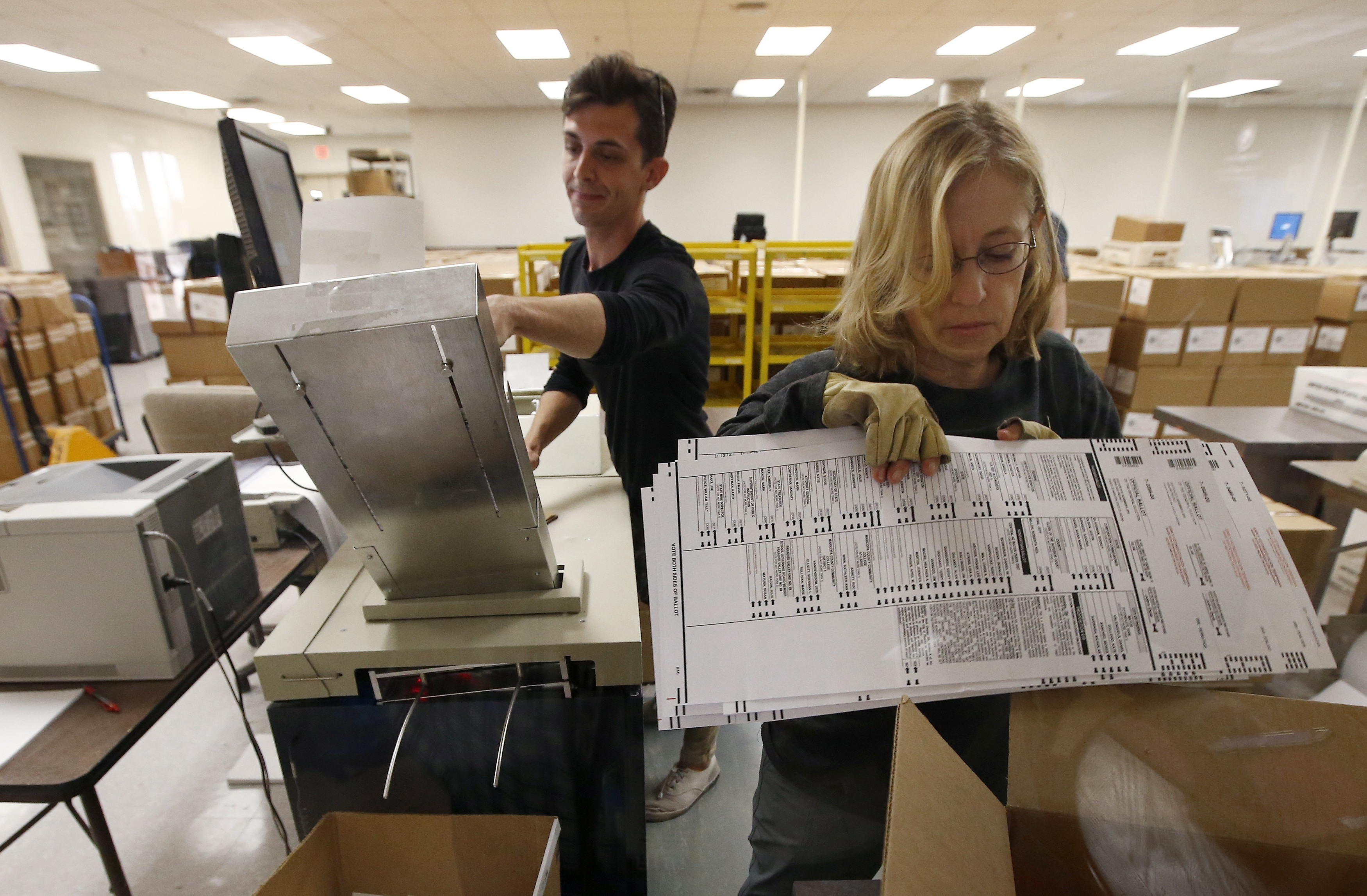 Workers organize ballots at the Maricopa County Recorder's Office Thursday, Nov. 8, 2018, in Phoenix. There are several races too close to call in Arizona, especially the Senate race between Democratic candidate Kyrsten Sinema and Republican candidate Martha McSally. (AP Photo/Ross D. Franklin)
