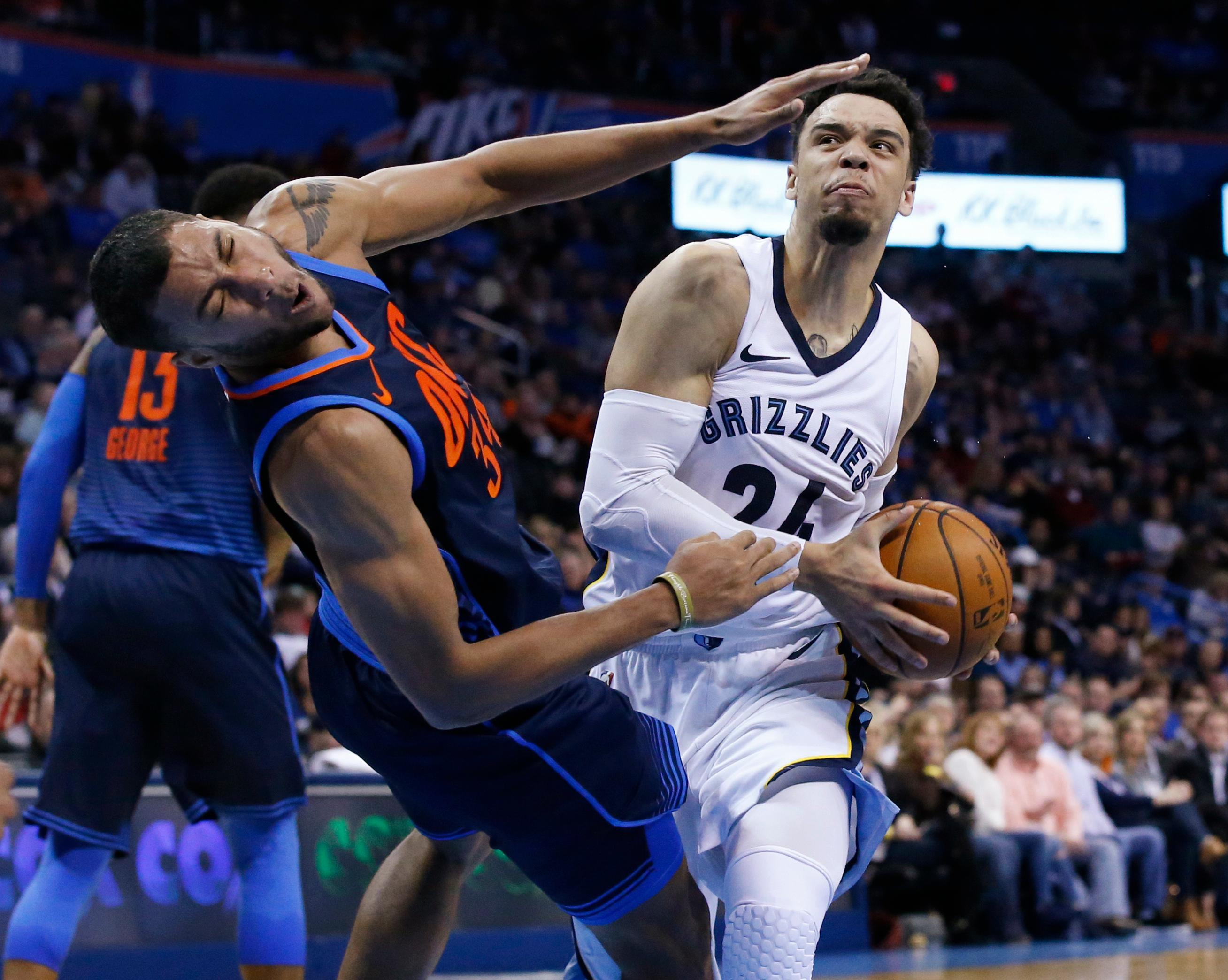 Oklahoma City Thunder forward Josh Huestis left, grimaces as he is fouled by Memphis Grizzlies forward Dillon Brooks, right, in the first half of an NBA basketball game in Oklahoma City, Sunday, Feb. 11, 2018. (AP Photo/Sue Ogrocki)