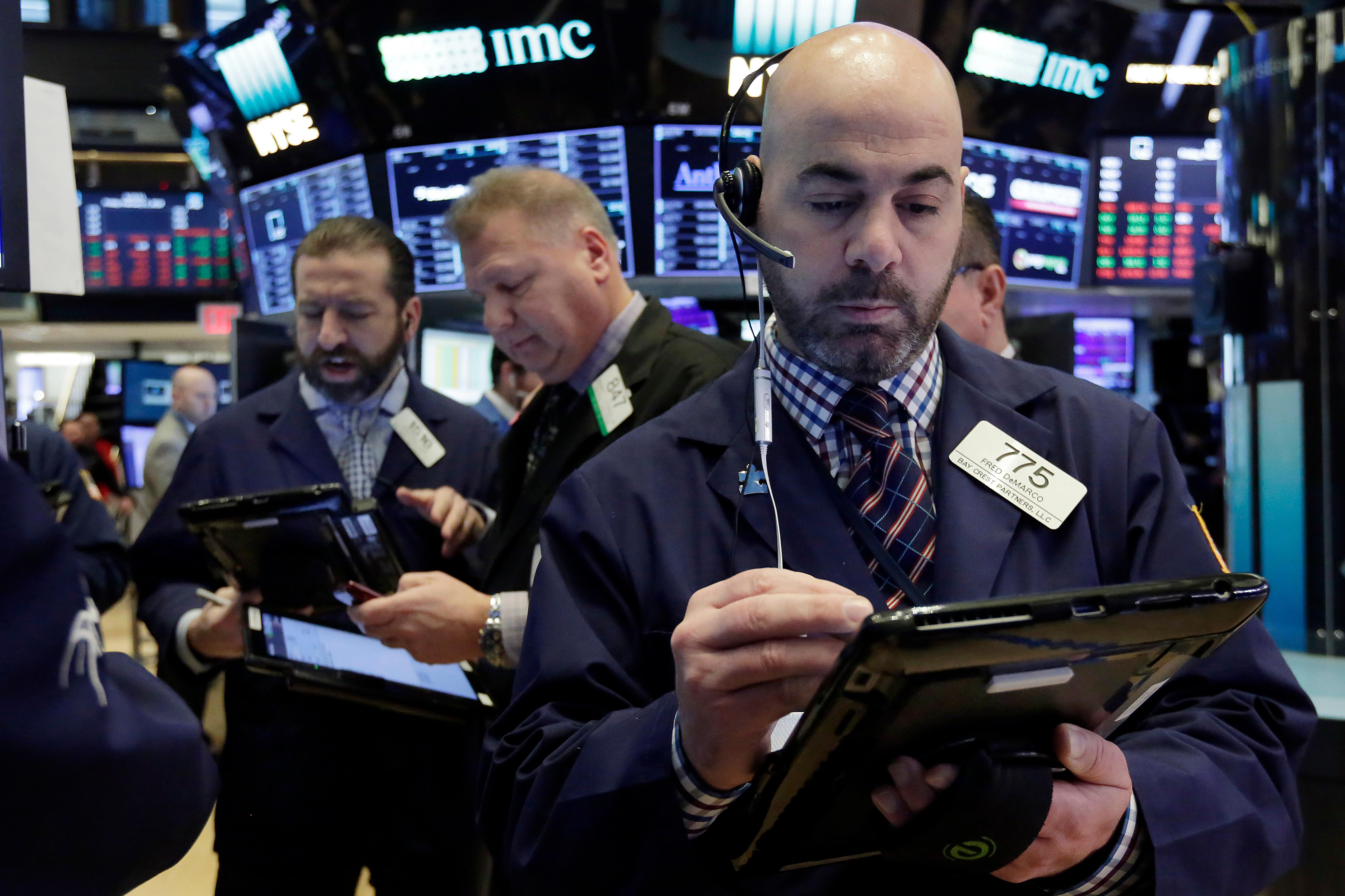 Fred DeMarco, right, works with fellow traders on the floor of the New York Stock Exchange, Friday, Feb. 2, 2018. Technology companies were leading stocks broadly lower in early trading, extending the market's slide into a second day. (AP Photo/Richard Drew)