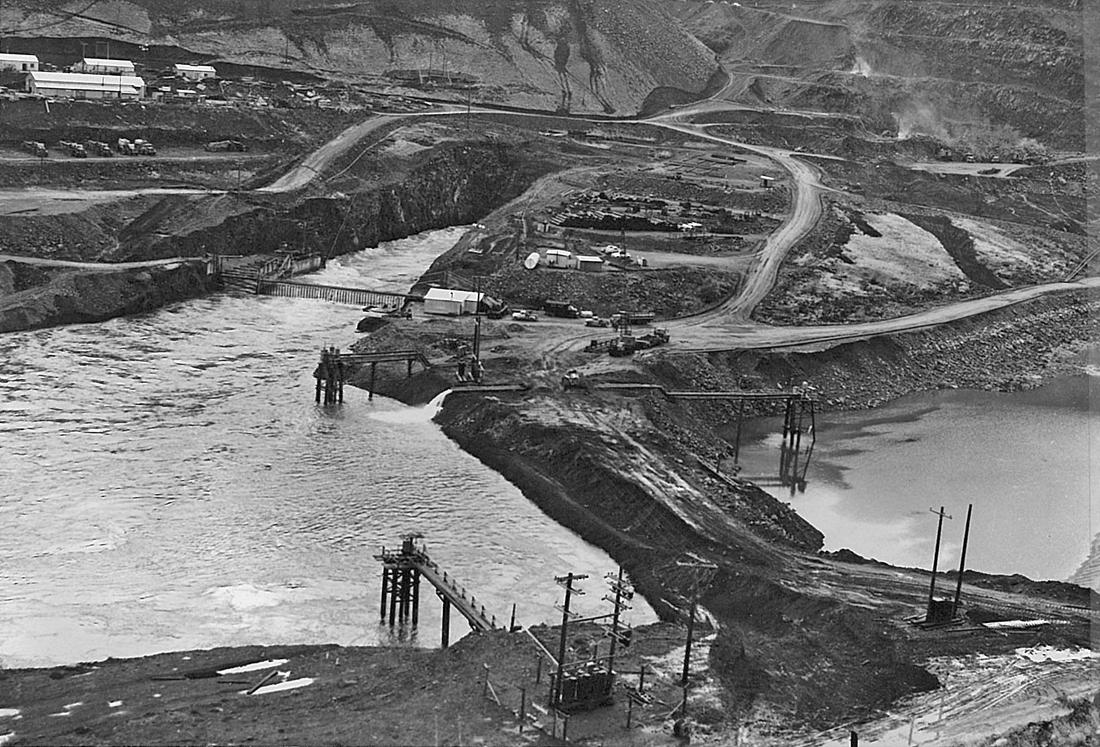 Brownlee Dam site during construction. Coffer dams are keeping water out of the construction area of the old channel. Residual water is being pumped out via a big hose in the center of the photo. (Idaho Power Company)