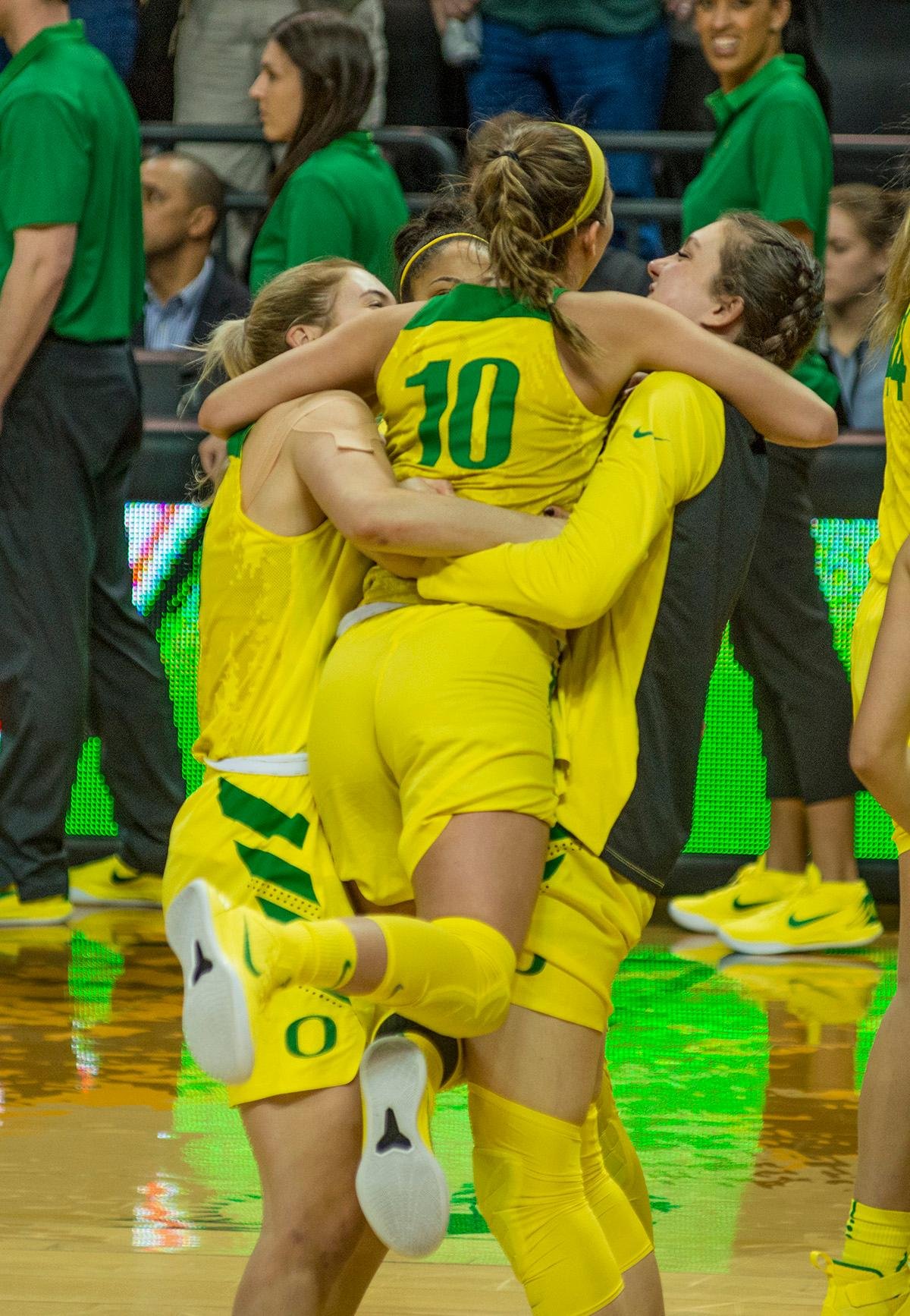 Oregon Ducks Lexi Bando (#10) celebrates with her teammates after their win over the USC Trojans. The Oregon Ducks defeated the USC Trojans 80-74 on Friday at Matthew Knight Arena in a game that went into double overtime. Lexi Bando sealed the Ducks' victory by scoring a three-pointer in the closing of the game. Ruthy Hebard set a new NCAA record of 30 consecutive field goals over three games, the old record being 28. Ruthy Hebard got a double-double with 27 points and 10 rebounds, Mallory McGwire also had 10 rebounds. The Ducks had four players in double digits: Ruthy Hebard with 27; Maite Cazorla with 17; Sabrina Ionescu with 15; and Lexi Bando with 11. The Ducks are now 24-4, 13-2 in the Pac-12, and are tied for first with Stanford. Photo by Dan Morrison, Oregon News Lab