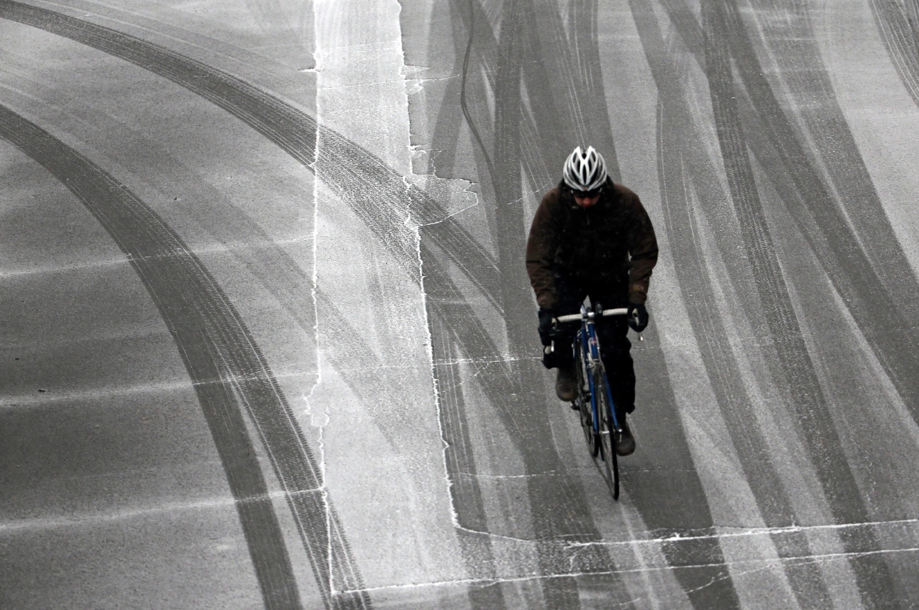 A lone bicyclist maneuvers on slick roads after a snow storm moved in on the area in Portland, Ore., Wednesday, Dec. 14, 2016. A wintry afternoon and evening is forecast for much of Oregon, with some cities expected to get a foot of snow. (AP Photo/Don Ryan)