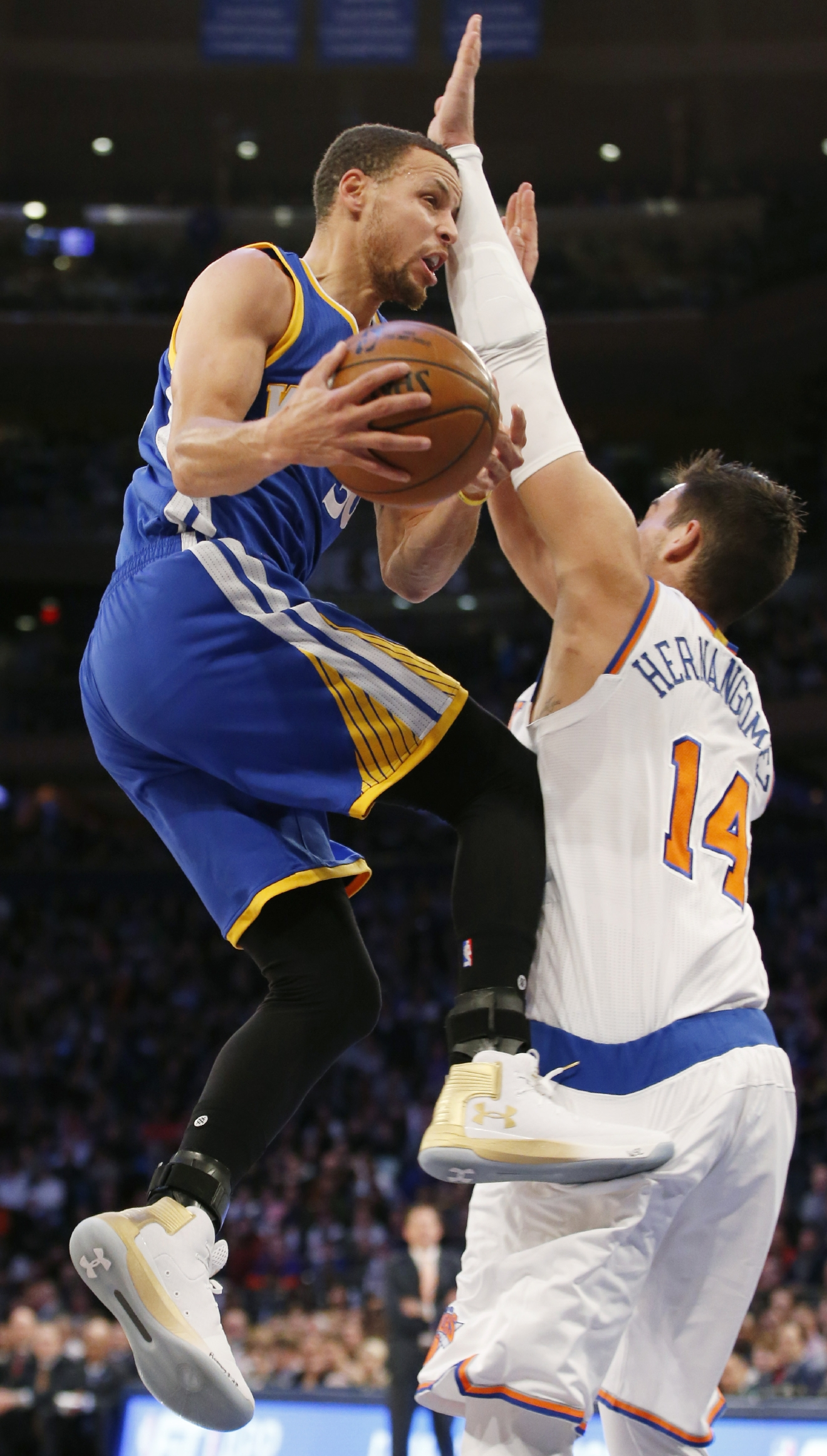 Golden State Warriors guard Stephen Curry, left, bumps into New York Knicks center Willy Hernangomez (14) as he goes up for a layup in the first half of an NBA basketball game at Madison Square Garden in New York, Sunday, March 5, 2017. (AP Photo/Kathy Willens)