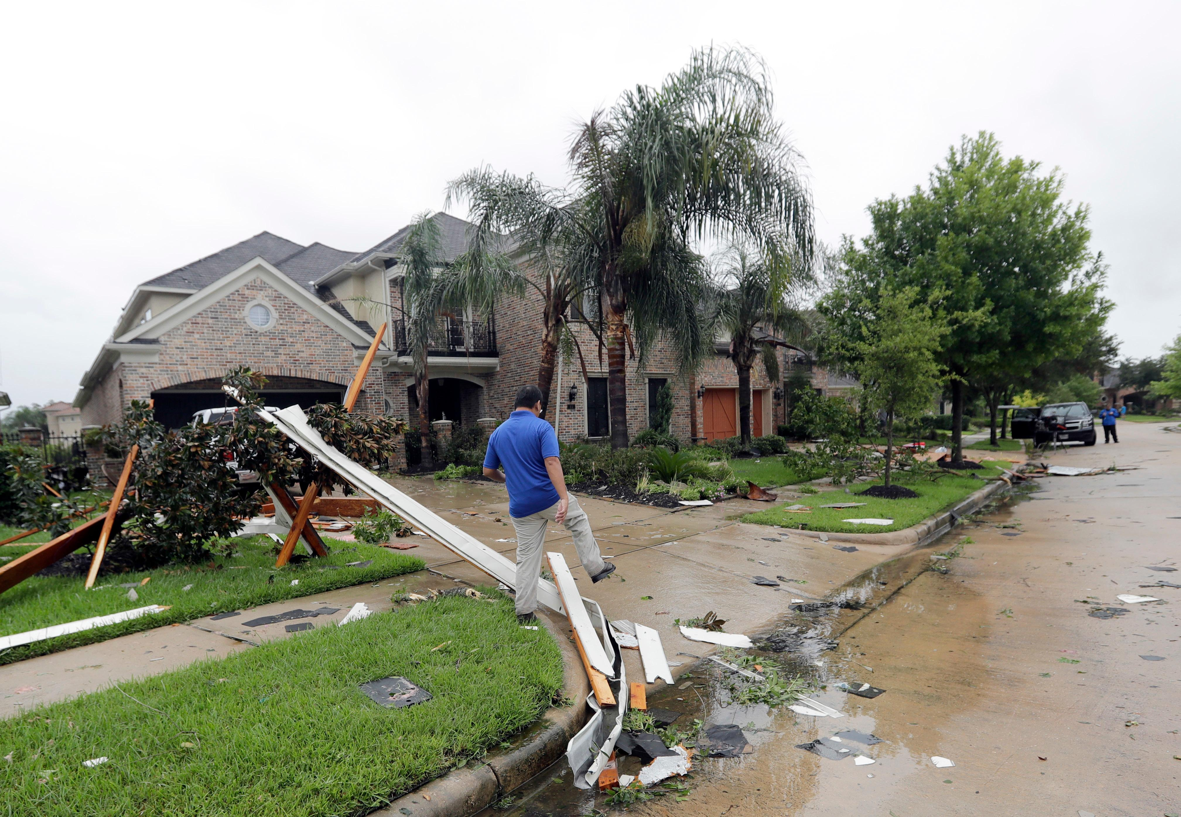 A contractor walks over debris from Hurricane Harvey Saturday, Aug. 26, 2017, in Missouri City, Texas.  Harvey rolled over the Texas Gulf Coast on Saturday, smashing homes and businesses and lashing the shore with wind and rain so intense that drivers were forced off the road because they could not see in front of them.  (AP Photo/David J. Phillip)