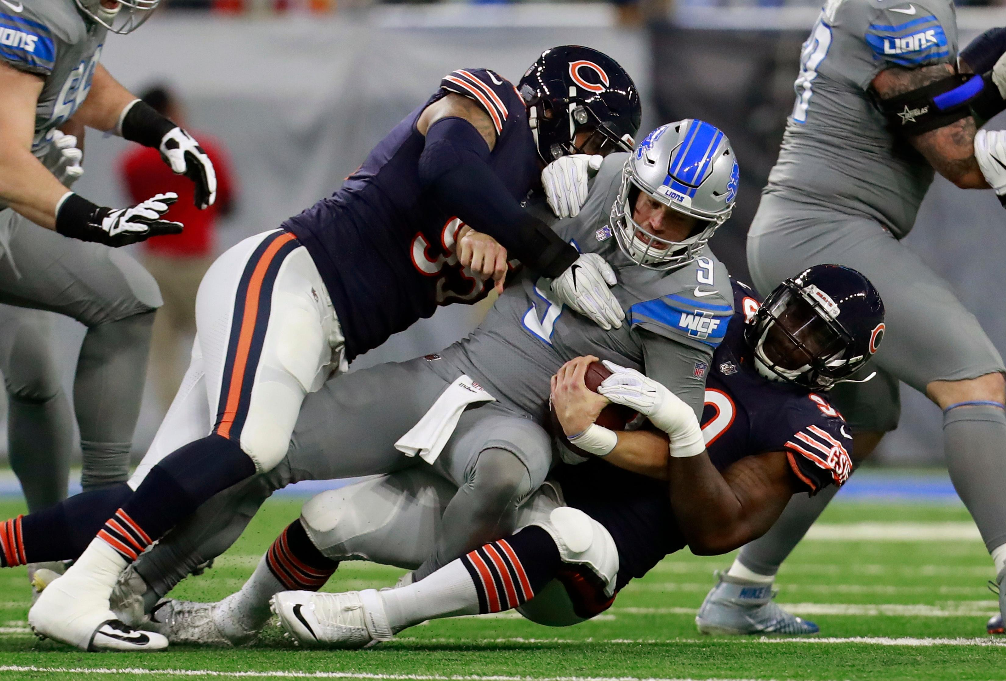 Detroit Lions quarterback Matthew Stafford (9) is sacked by Chicago Bears defensive end Roy Robertson-Harris, left, and linebacker Lamarr Houston during the first half of an NFL football game, Saturday, Dec. 16, 2017, in Detroit. (AP Photo/Rey Del Rio)